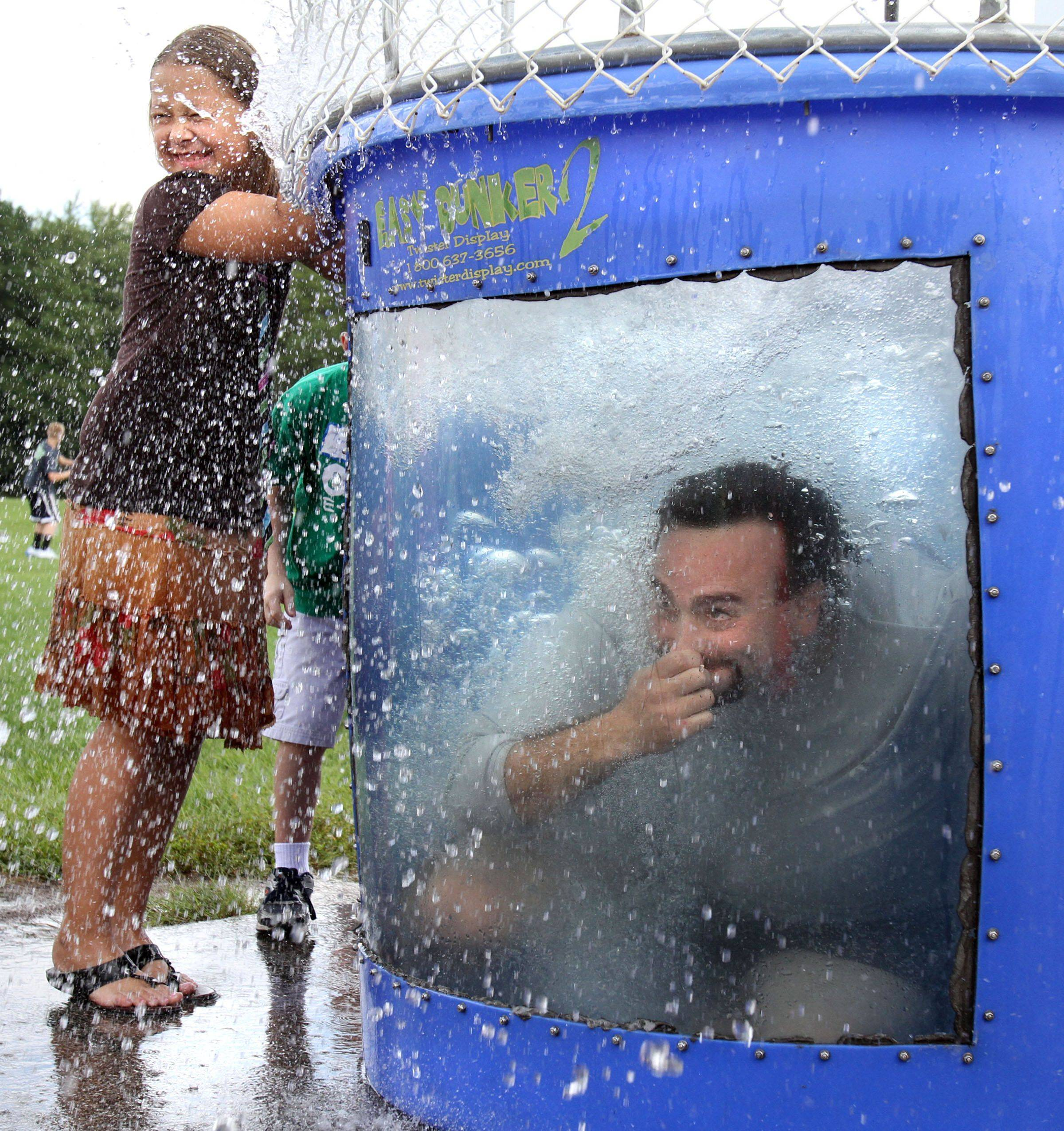 Fourth-grader Maja Keska gets splashed as Cameron Shapiro, principal of Seth Paine Elementary School, is dropped in the dunk tank at the school's 50th birthday party held by Lake Zurich Community Unit School District 95 at the school in Lake Zurich on Saturday.