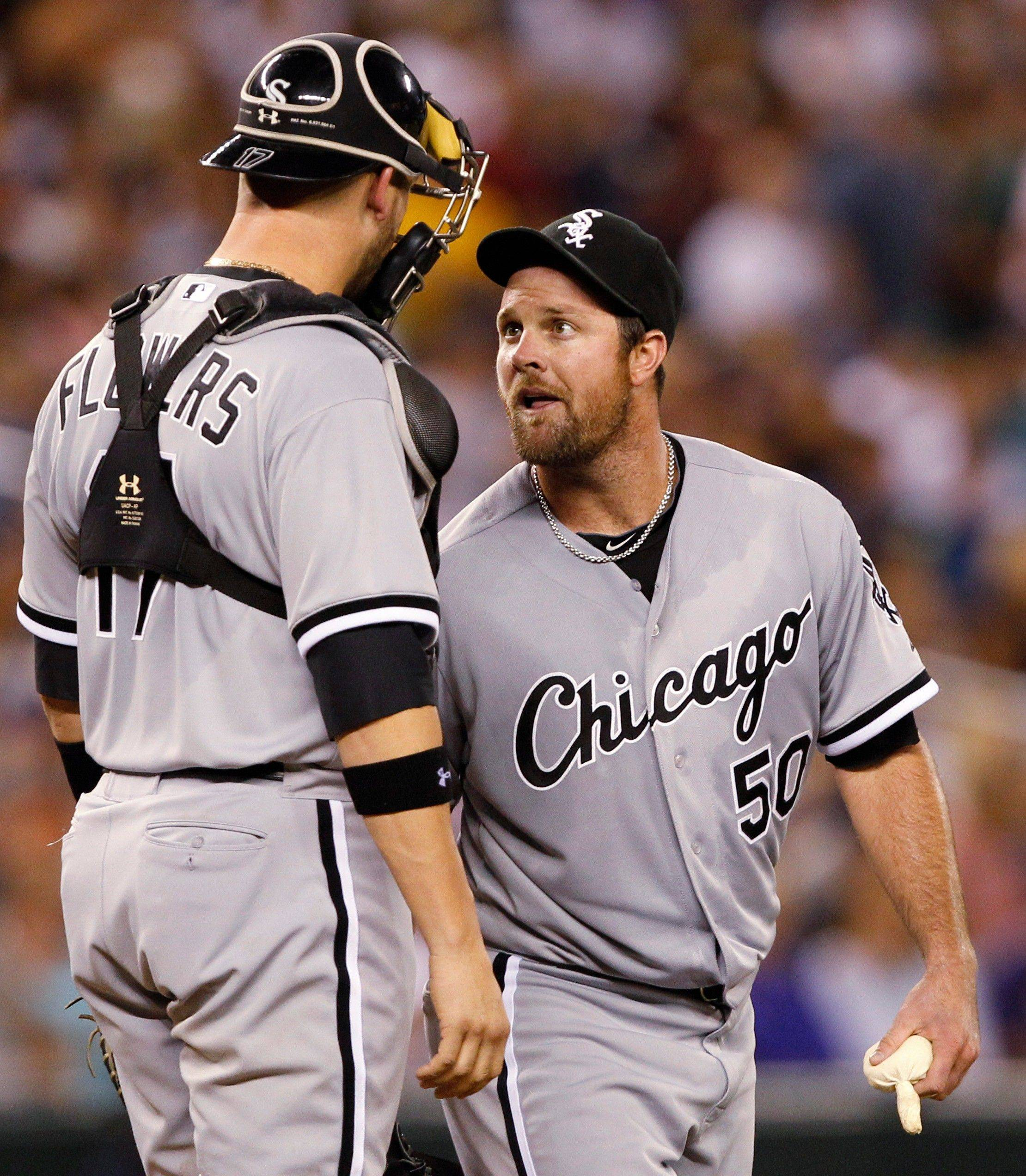 Chicago White Sox starting pitcher John Danks, right, talks with catcher Tyler Flowers after allowing a hit by the Seattle Mariners in the sixth inning of a baseball game on Saturday, Aug. 27, 2011, in Seattle. (AP Photo/Elaine Thompson)