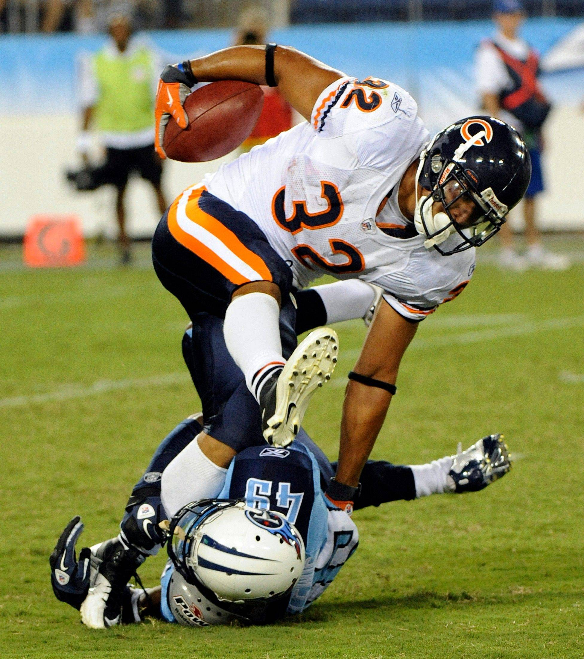 Chicago Bears running back Kahlil Bell (32) is tripped up by Tennessee Titans cornerback LeQuan Lewis (49) in the third quarter of an NFL football preseason game Saturday, Aug. 27, 2011, in Nashville, Tenn. (AP Photo/Frederick Breedon)