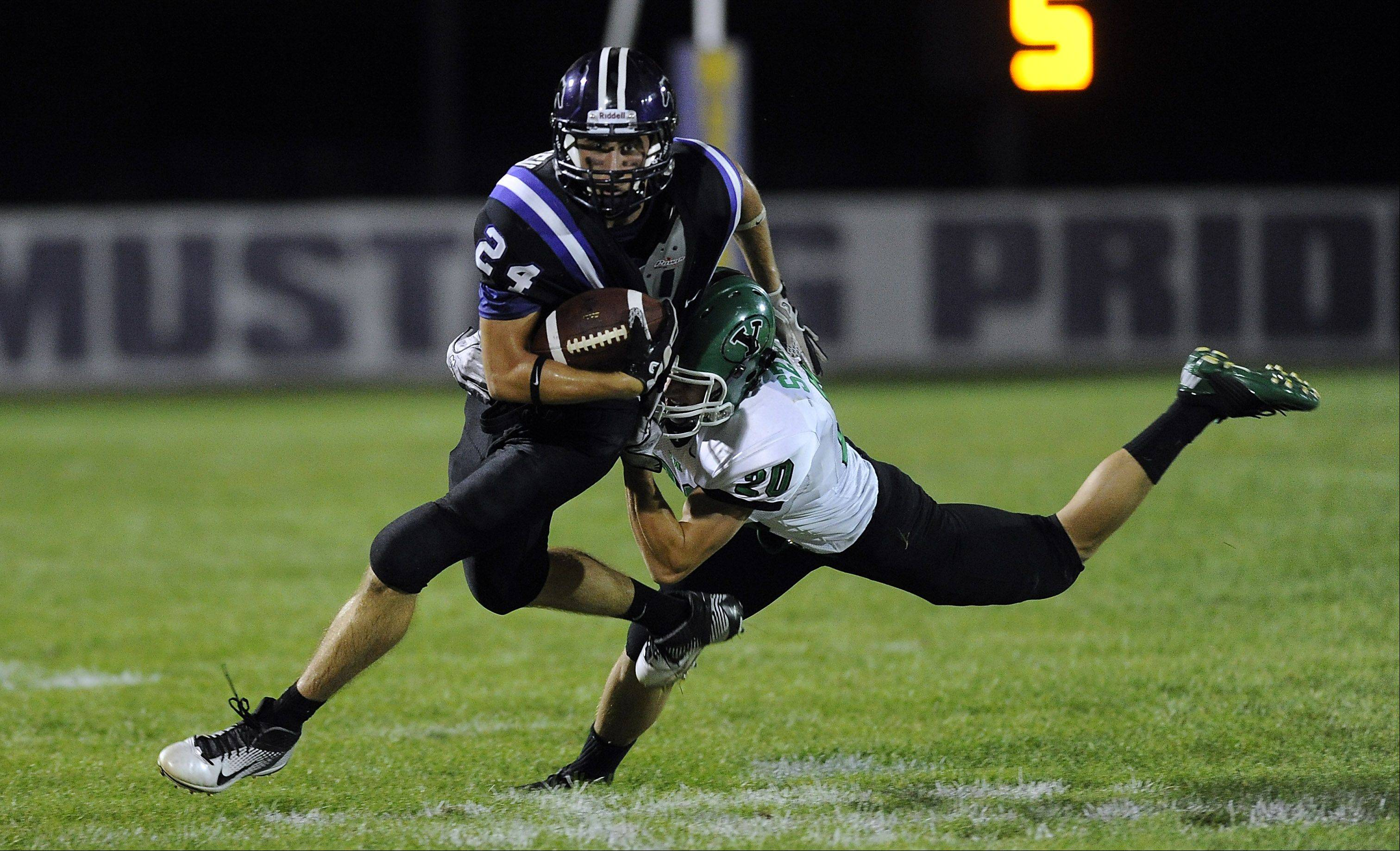 Rolling Meadows Ryan Gundersen is tackled by York's Kevin Szeluga in the second quarter of play in opening night of Friday night football in the northwest suburbs.
