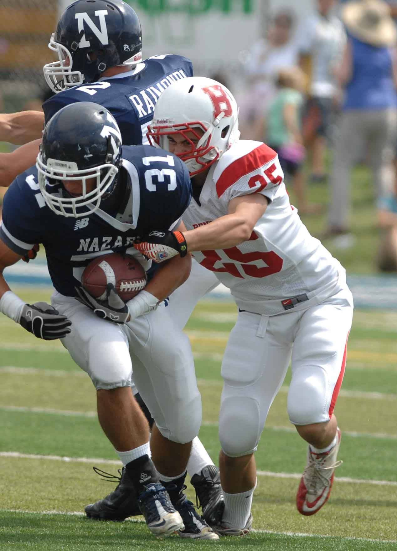 Porter Ontko of Benet pulls down Rudy Romagnano of Nazareth during the Benet at Nazareth football Saturday in LaGrange Park.
