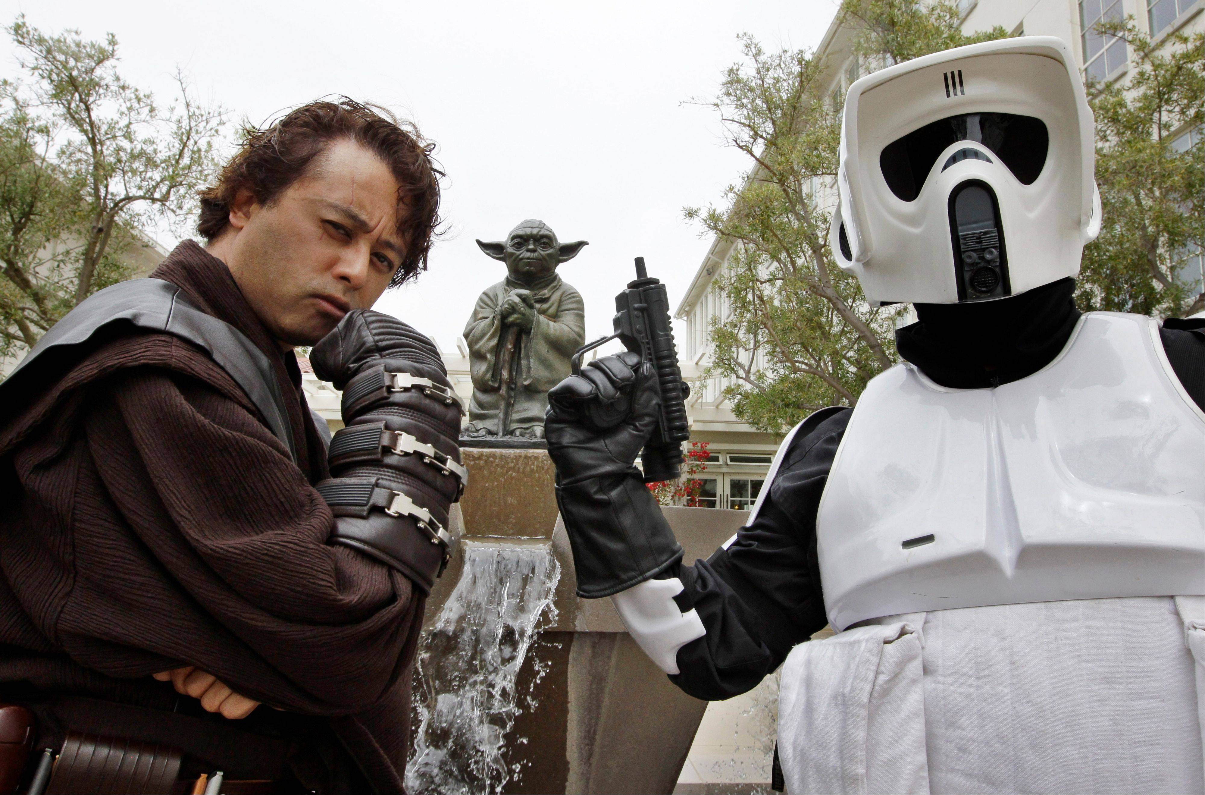 Matt Tolosa, left, wearing an Anakin Skywalker costume, and his brother Dale Tolosa, dressed as a Stormtrooper, pose in front of a life-size replica of Yoda in San Francisco.