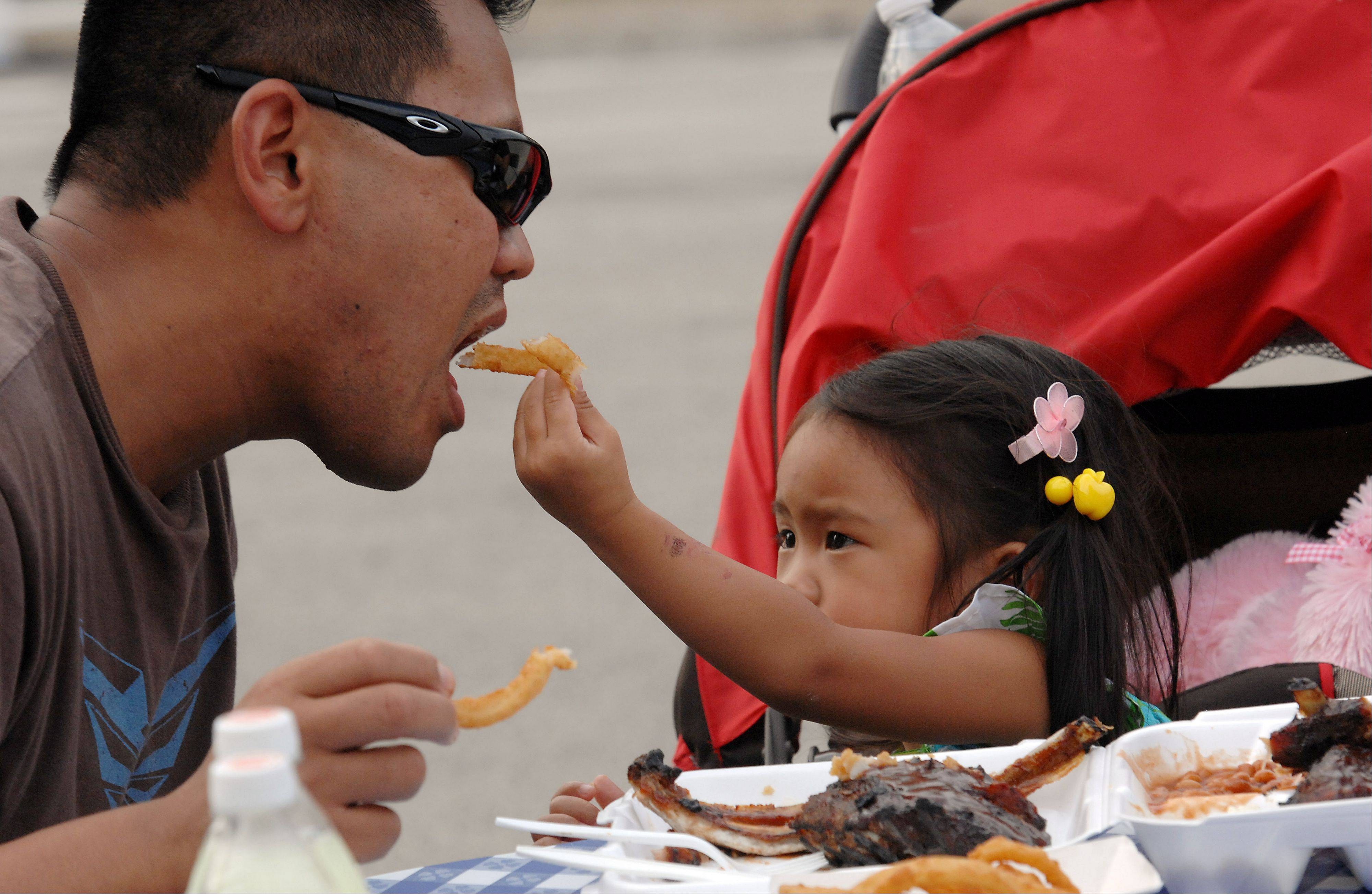 Sharing is caring- Jasmine Lucero, 2, of South Elgin gives her onion ring but none of her ribs to her dad, Joel, at the Palatine Streetfest on Friday.