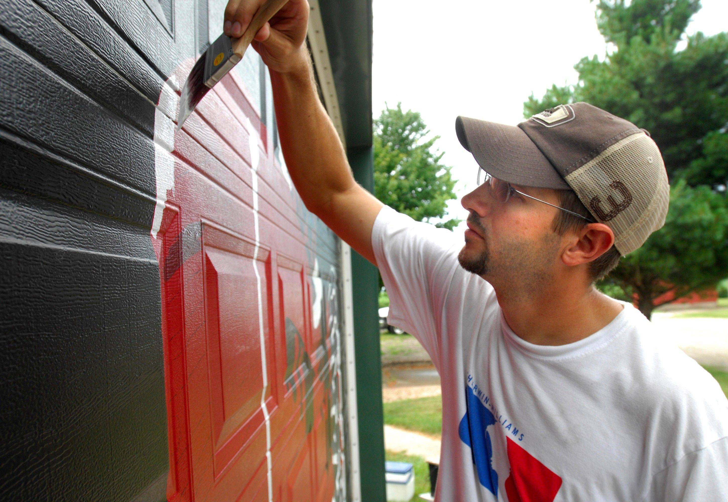 Barn artist Scott Hagan paints a tractor on a garage door at Jo Morrison's barn east of Towanda, Ill. Hagan has painted between 300 and 400 barn signs since beginning his carrer in 1997. (