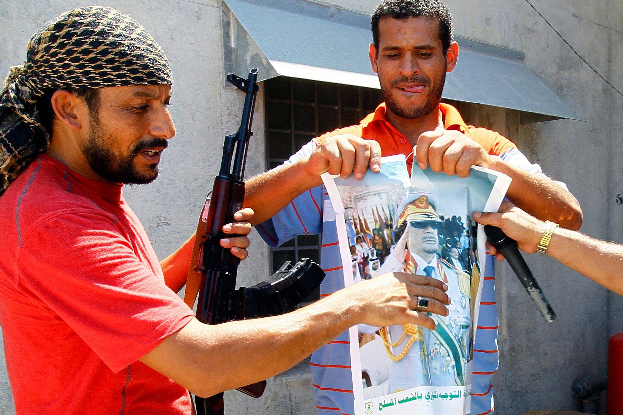 Libyan rebels tear up a portrait of Moammar Gadhafi on Wednesday inside his compound Bab al-Aziziya in Tripoli.