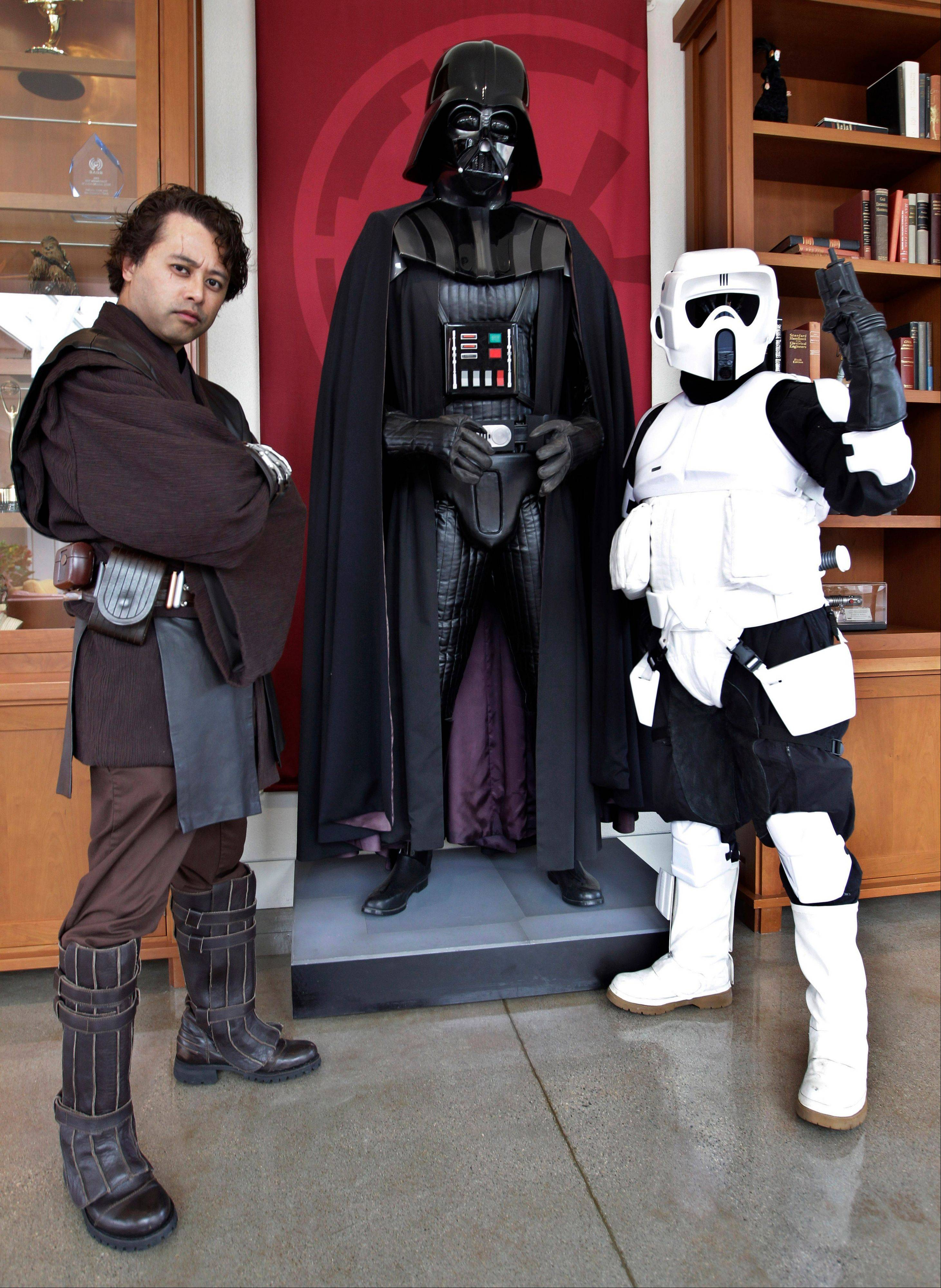 Matt Tolosa, left, wearing an Anakin Skywalker costume, and his brother Dale Tolosa, dressed as a Stormtrooper, pose with a Darth Vader mannequin.