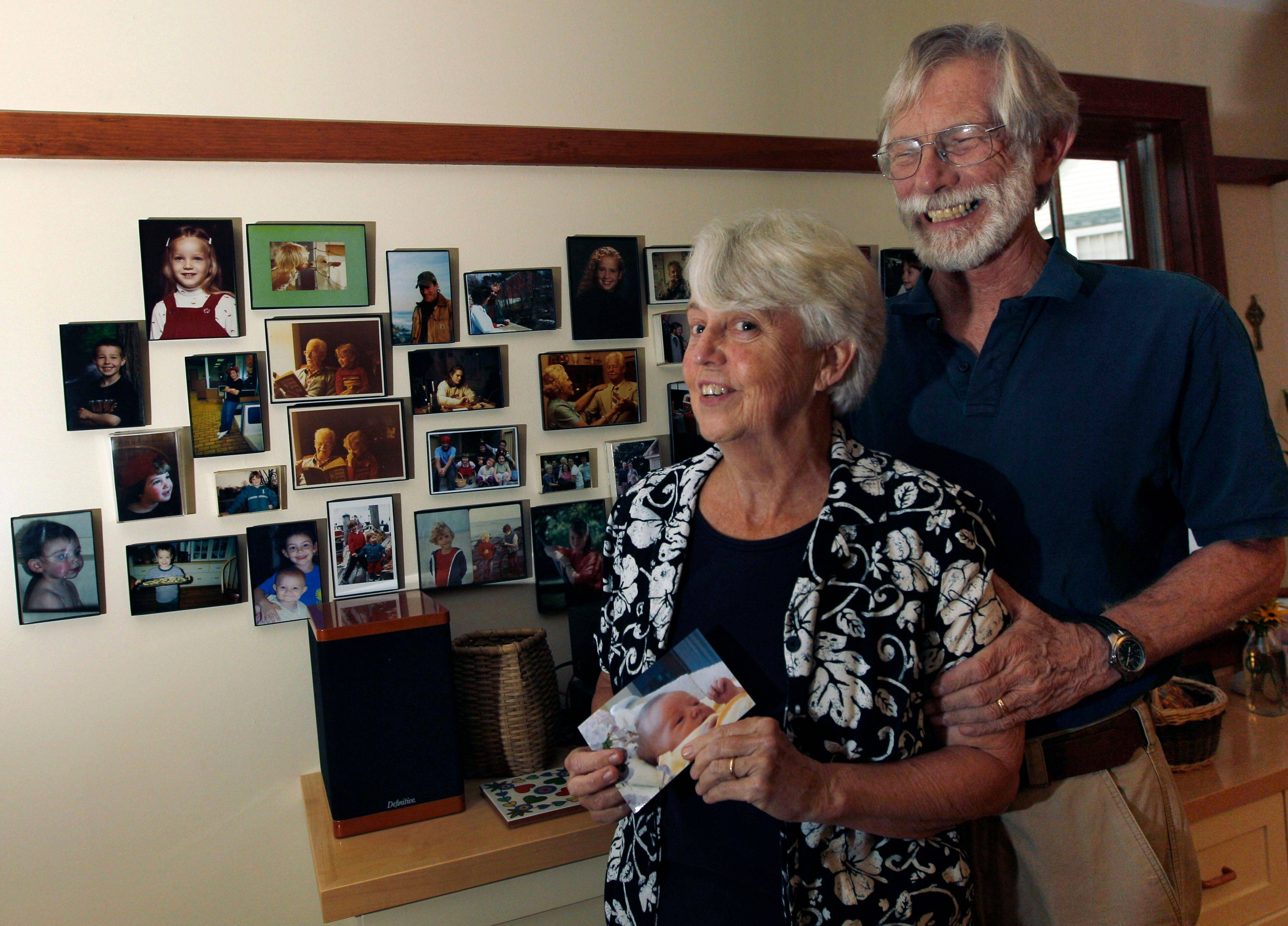 Eileen and Doug Flockhart laugh as she holds a picture of their seventh grandchild near a wall full of family photos in their home in Exeter, N.H.