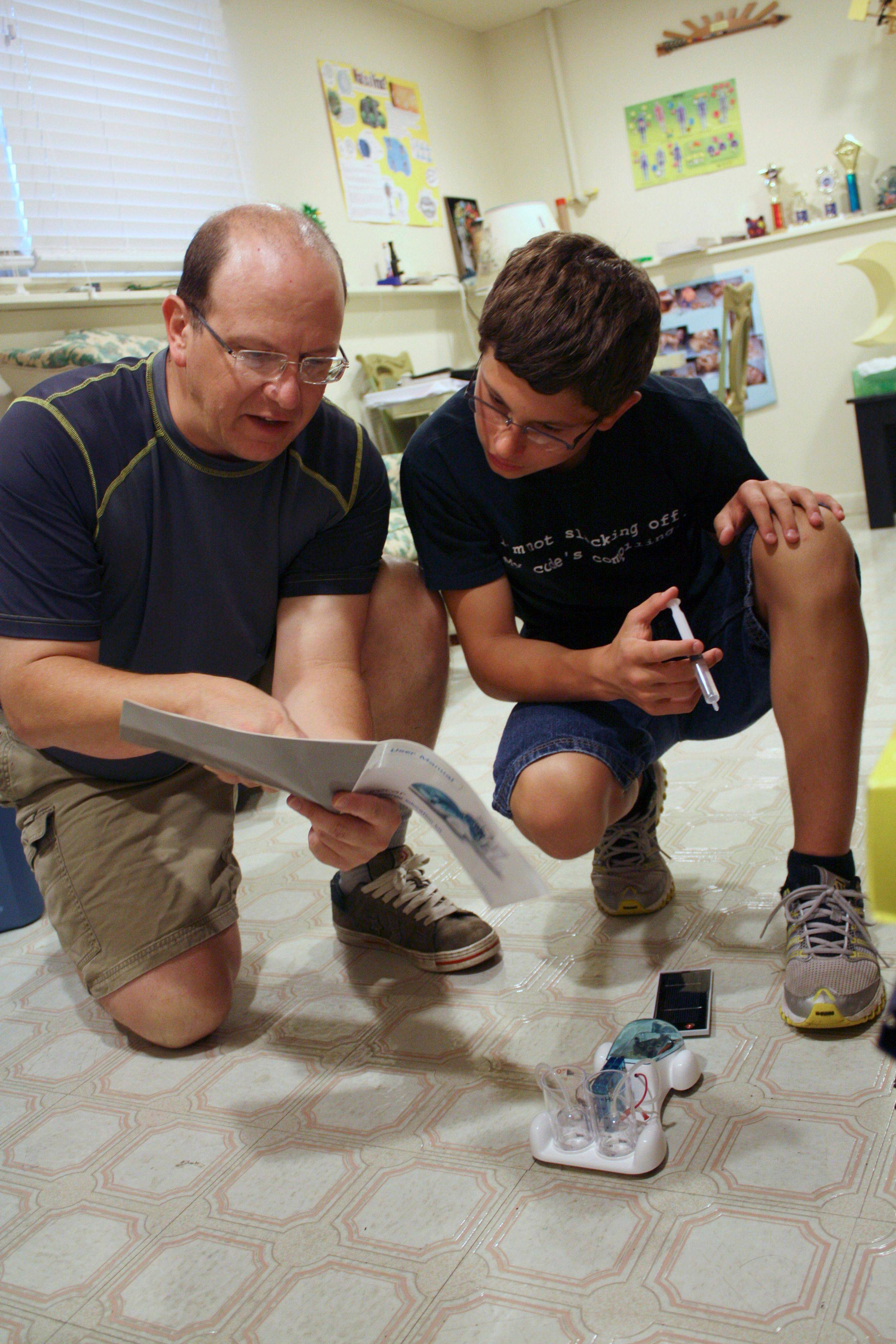 Noah Egler, 13, and his father, Mark, work together on a science experiment in the basement of their home in Bourbonnais.