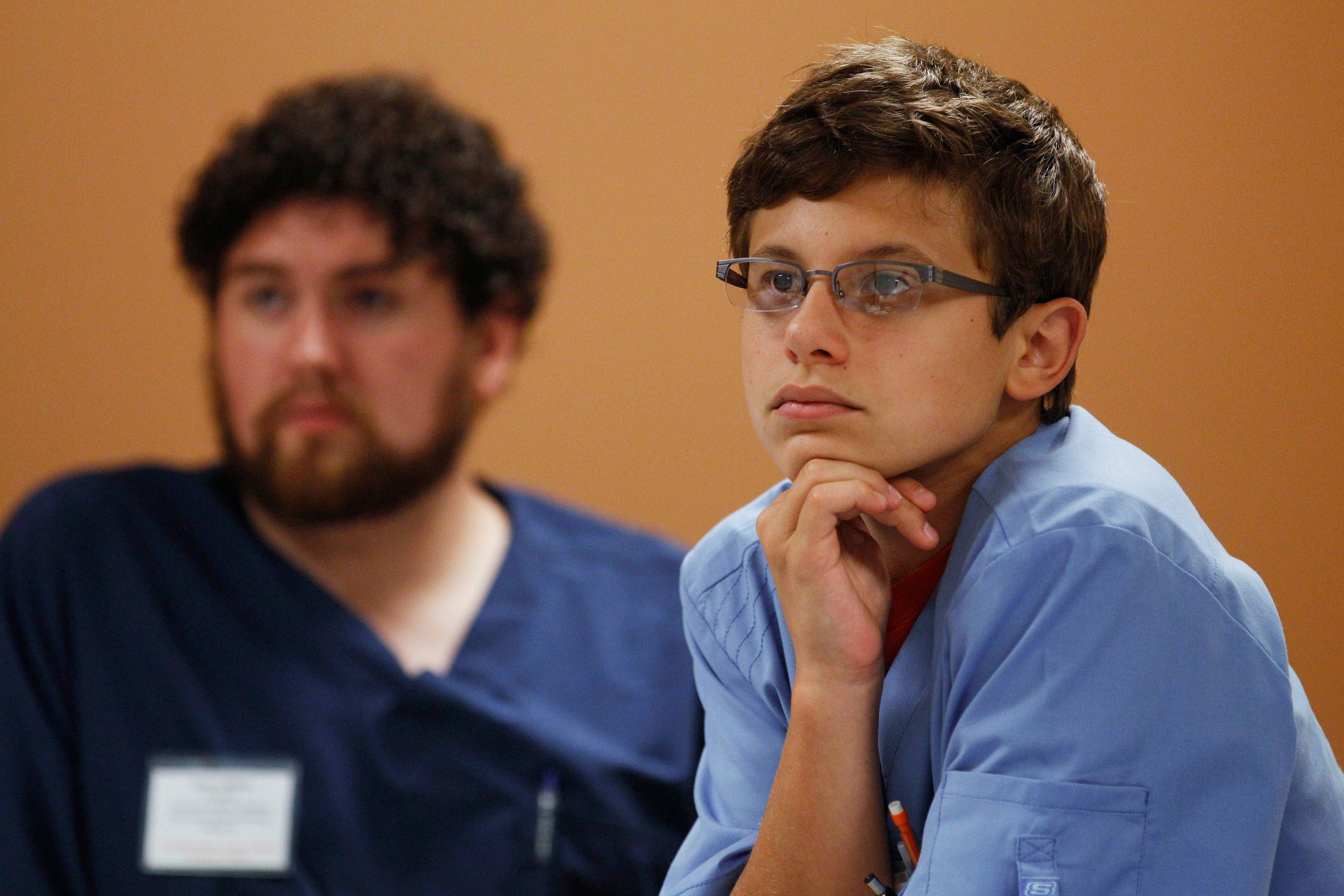 Noah Egler listens Aug. 2 during a workshop on electronic prosthetics at the Indiana University Northwest medical school in Gary, Ind. At left is Egler's lab partner Jarod Markley.