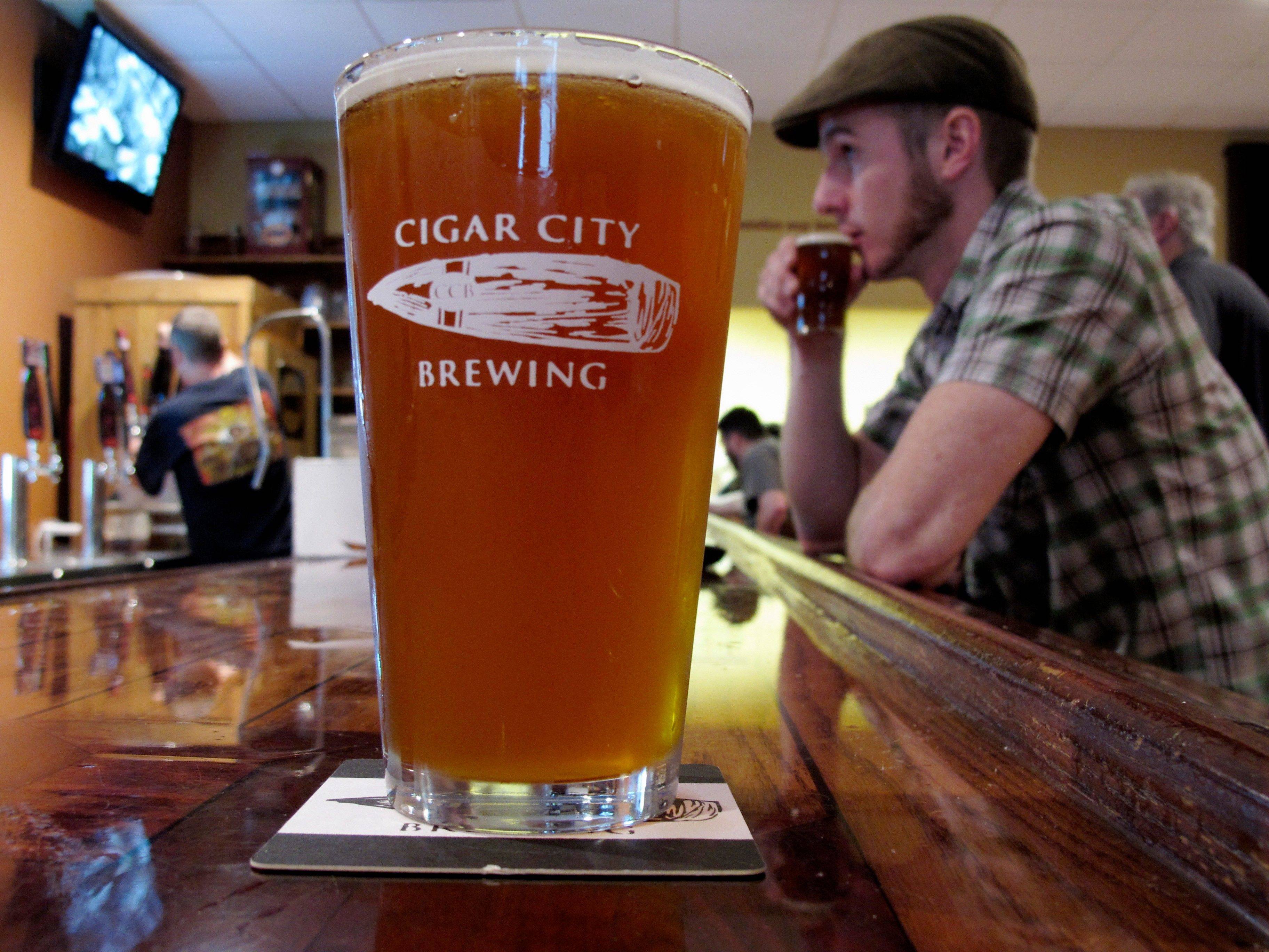 A pint of Cigar City beer is shown on the bar at the brewery's tasting room in Tampa, Fla. Cigar City uses ingredients such as Spanish cedar, guava, Cuban espresso and citrus woods to craft beers that also taste of Tampa's heritage.