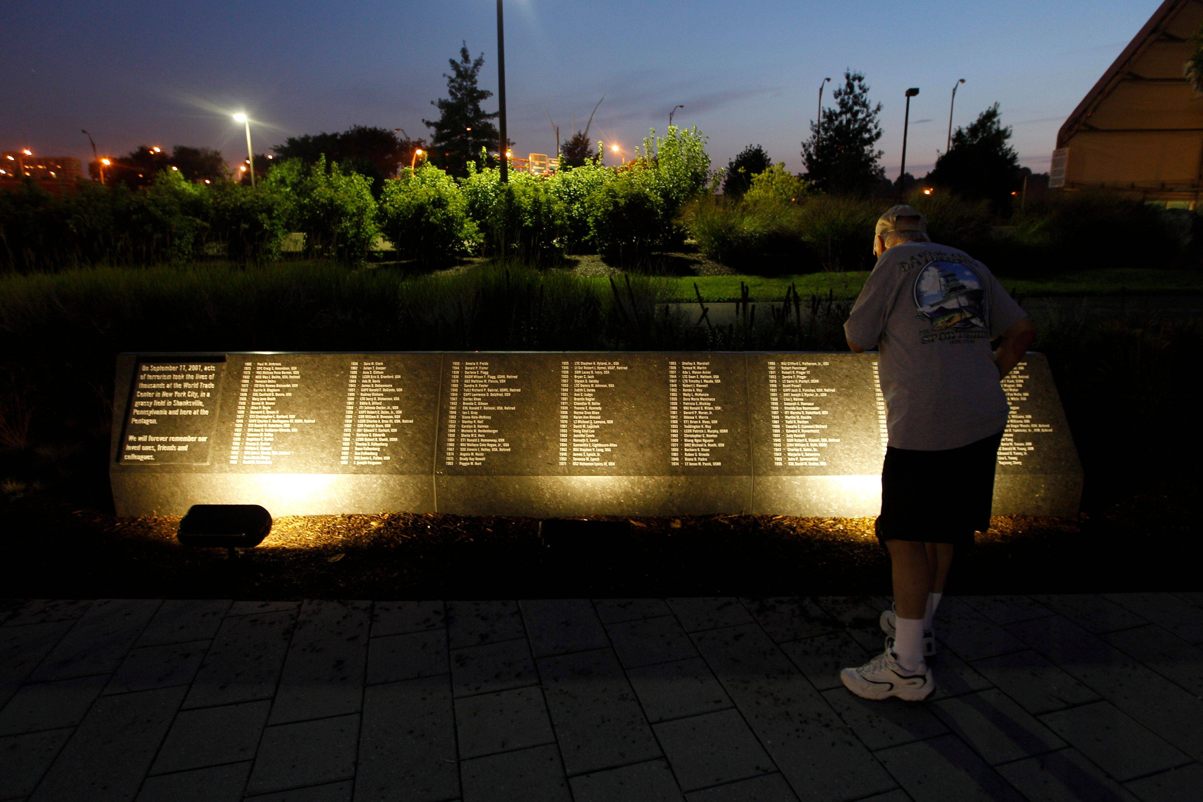 A visitor to the Pentagon Memorial reads the names of people who died on Sept. 11, 2001, in the terrorist attack on the Pentagon in Arlington, Va. The Pentagon was the first of the three attack sites to open an official memorial. It was dedicated Sept. 11, 2008.
