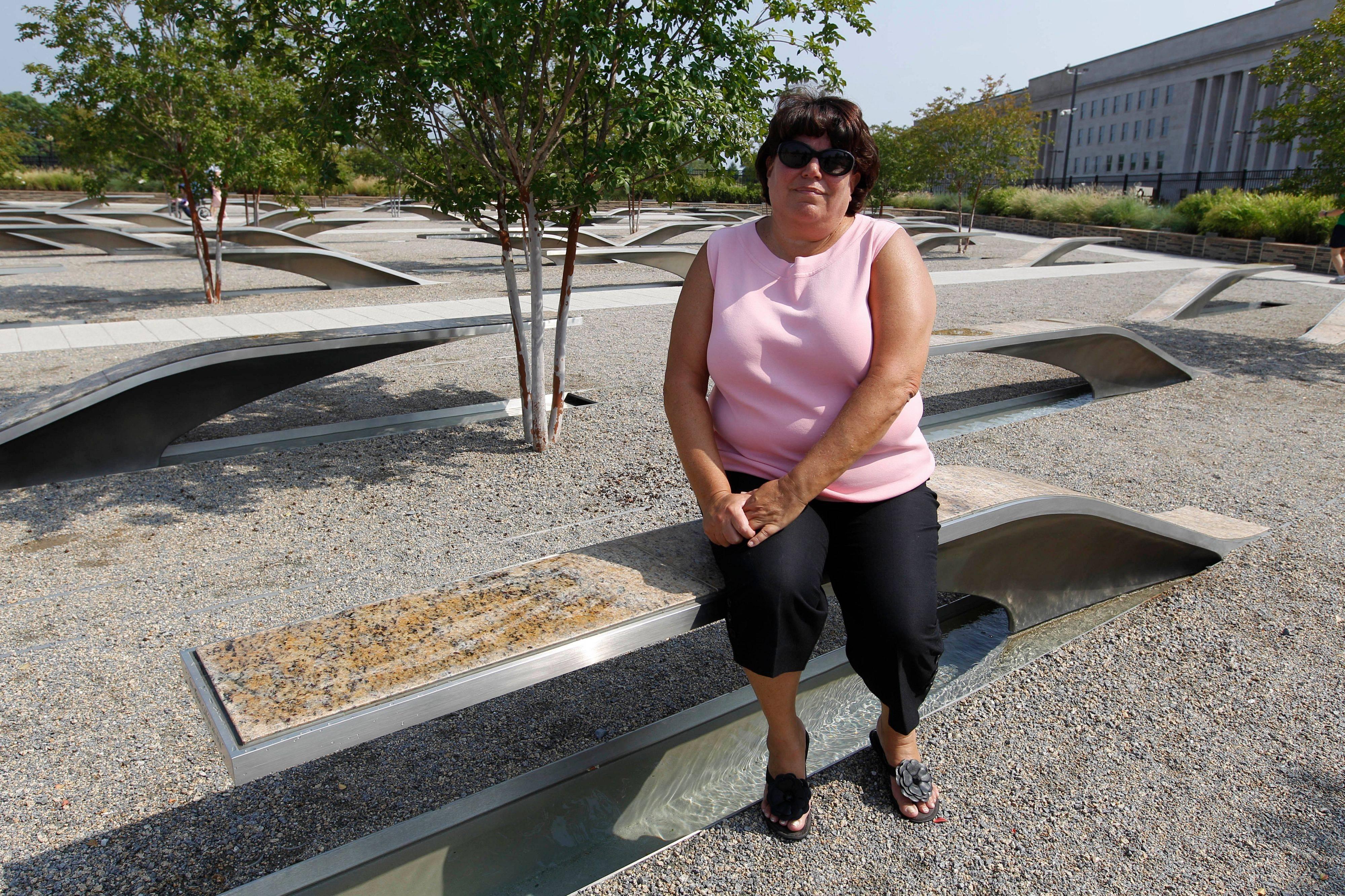 Volunteer docent Lisa T. Dolan sits on the bench that bears the name of her late husband, Navy Capt. Robert E. Dolan Jr., who died Sept. 11, 2001, in the terrorist attack on the Pentagon in Arlington, Va.