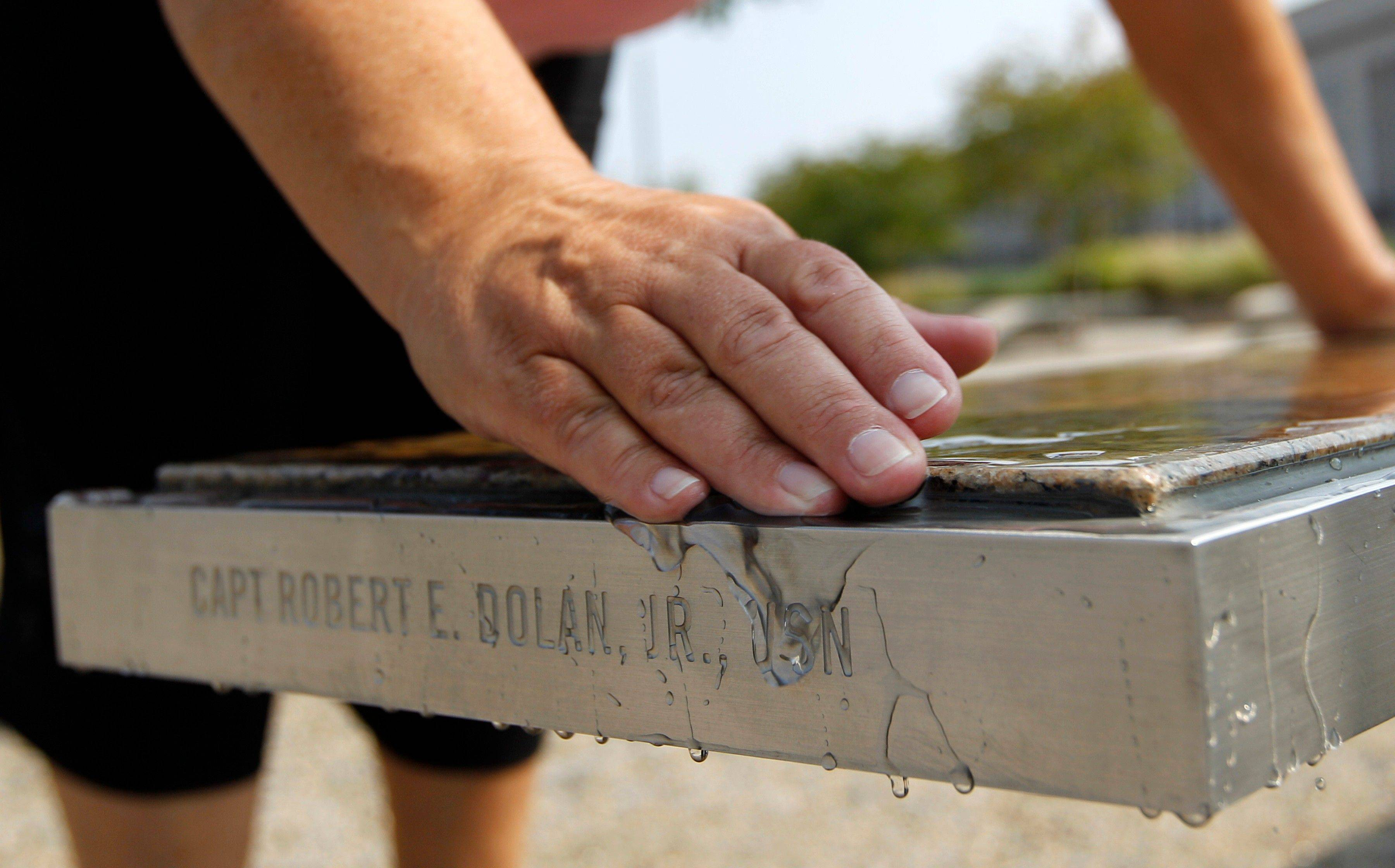 Volunteer docent Lisa T. Dolan wipes water off the bench that bears the name of her late husband, Navy Capt. Robert E. Dolan Jr., at the Pentagon Memorial in Arlington, Va.
