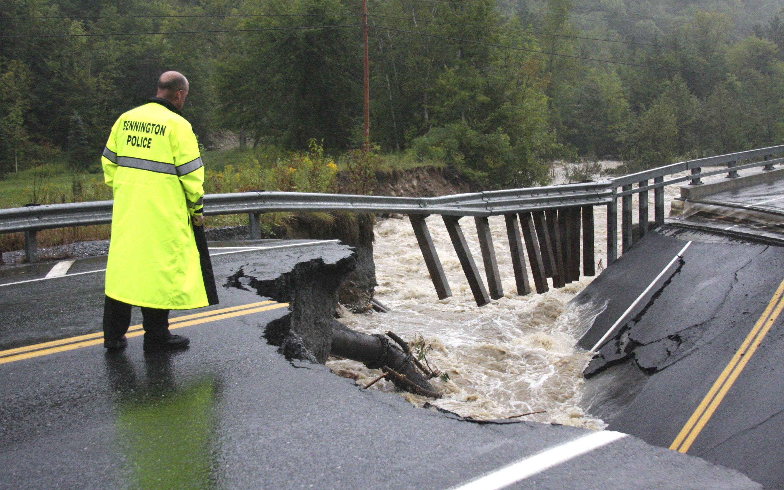 Bennington Police Chief Paul Doucette looks at a collapsed bridge on Route 9 in Woodford, Vt. on Sunday. The remnants of Hurricane Irene dumped torrential rains on Vermont on Sunday, flooding rivers and closing roads from Massachusetts to the Canadian border.