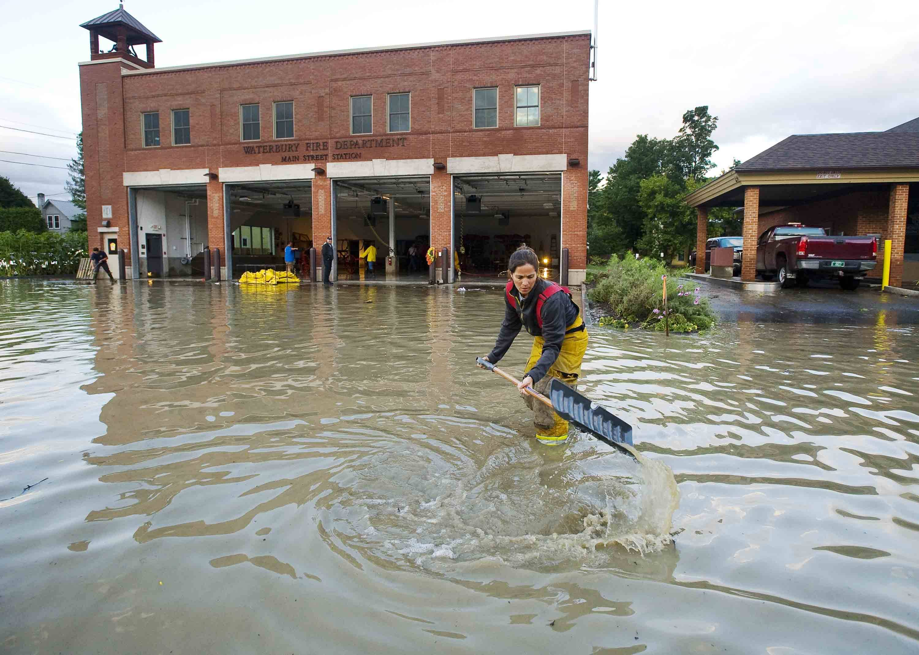 Firefighter Mandy Drake clears a storm drain in front of the fire department in Waterbury, Vt., in the wake of tropical storm Irene on Monday. The building was evacuated as high water from the Winooski River flooded the downtown area Sunday.