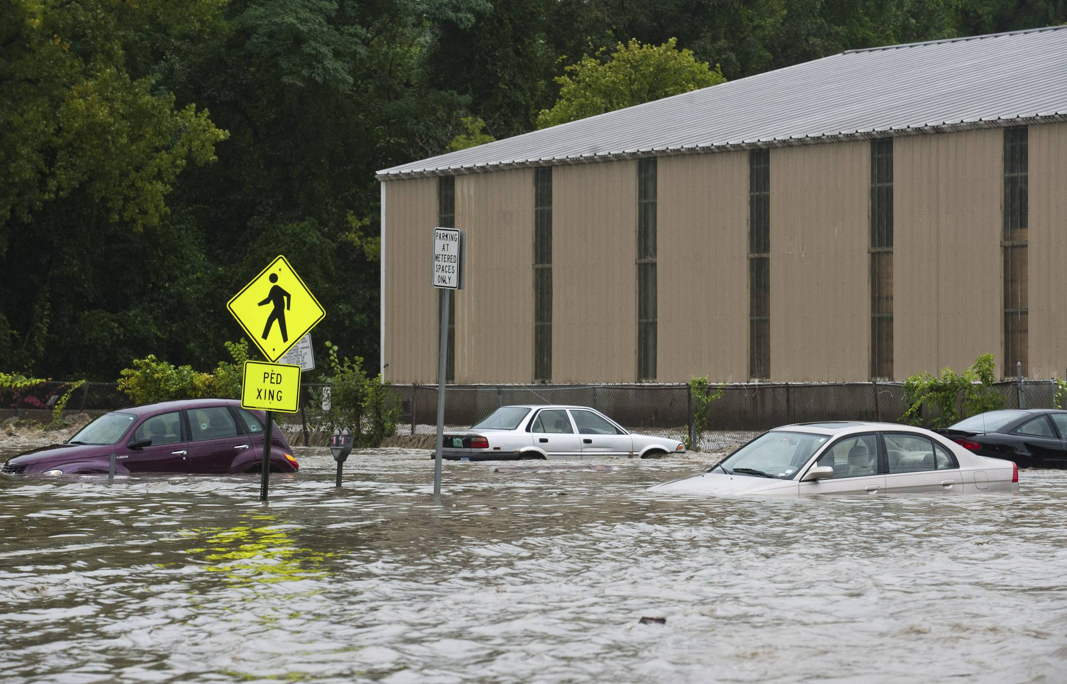 Cars in the parking lot at the bottom of Canal Street in Brattleboro, Vt., are submerged nearly to their windows by the flooding Whetstone Brook  on Sunday.