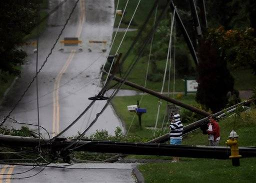 Residents on Foster Street in South Windsor, Conn., look over the mess of wires and down utility poles that were brought down during Irene, the hurricane that weakened to a tropical storm, Sunday, Aug. 28, 2011.