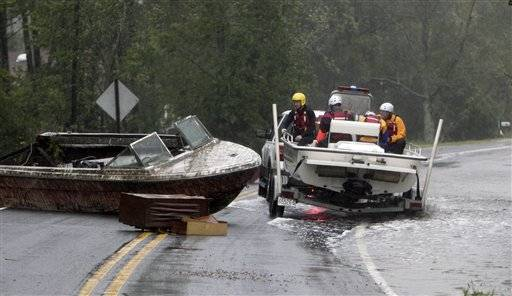 The Arr-Mac water rescue team from Wayne County maneuvers around a beached boat in the middle of Hwy. 304 Saturday, Aug. 27, 2011 in Mesic, N.C. Hurricane Irene knocked out power and piers in North Carolina, clobbered Virginia with wind and churned up the coast Saturday to confront cities more accustomed to snowstorms than tropical storms.