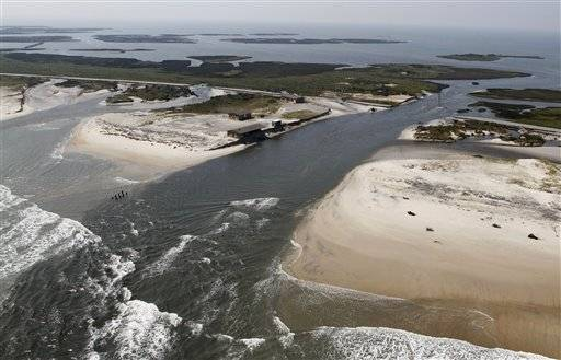 A flooded road is seen in Hatteras Island, N.C., Sunday, Aug. 28, 2011, after Hurricane Irene swept through the area Saturday cutting the roadway in five locations.