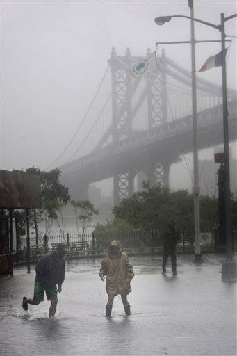 Eddie Lima, left, and Nancy Zakhary wade through a flooded area near the Brooklyn Bridge in New York to take some pictures.