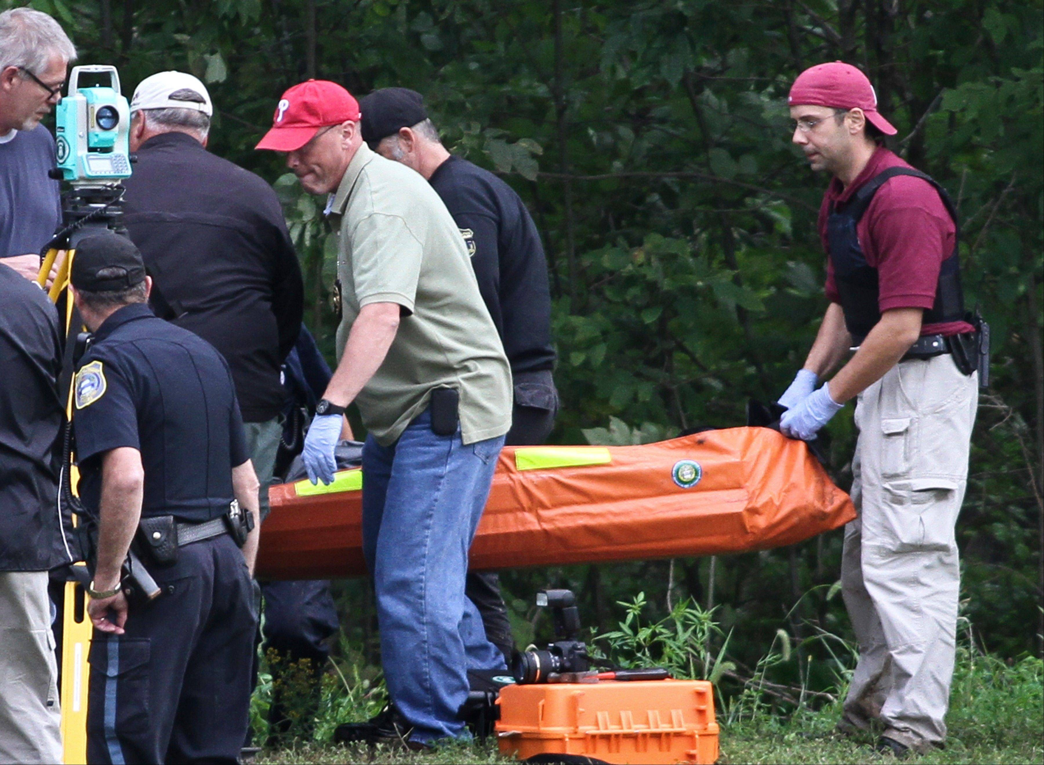 Investigators carry the body of Leonard John Egland from a wooded area in Warwick Township Pa., on Sunday, where he had been sought by police since early morning. Egland, who is suspected of killing four people in Pennsylvania and Virginia, was found dead of an apparently self-inflicted gunshot wound in suburban Philadelphia after a daylong manhunt during which he fired at and injured officers, authorities said.