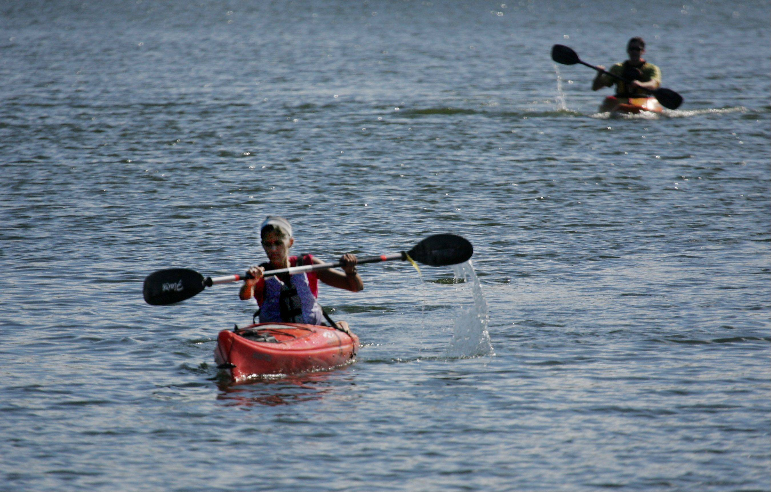 Emily Gregorich of Mundelein paddles to the finish during the Floating Zucchini Kayak Relay Races Sunday at Twin Lakes Recreation Area in Palatine. The event raised money for Smart Farms of Barrington that advocates sustainable gardening.