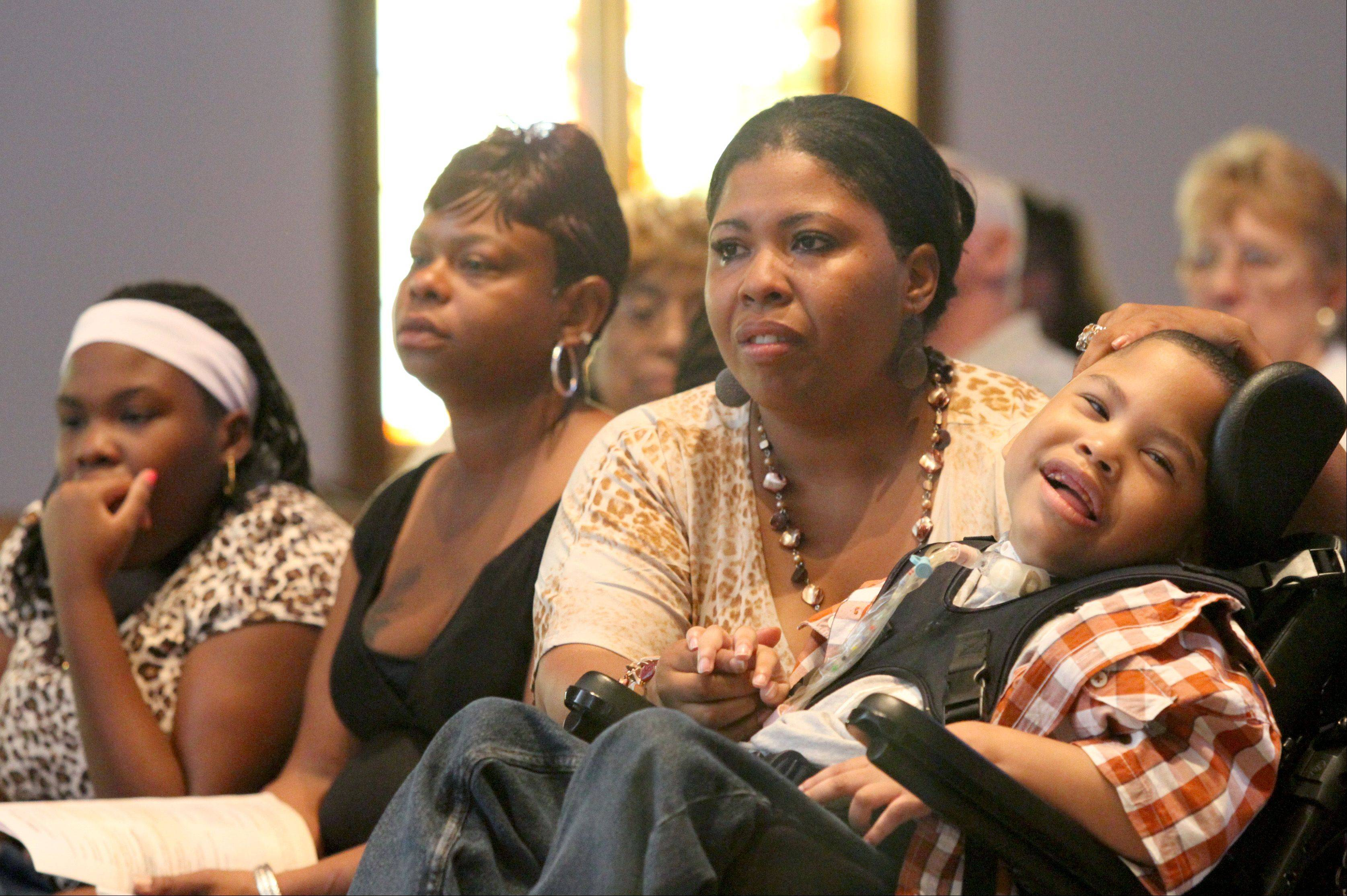 Cabri Moore, 11, from left, Beatrice Kimbrough, Debrina Moore and Christian Moore, 5, watch a Celtic dance performance during a benefit concert Sunday at the Lutheran Church of the Master in Carol Stream. The benefit concert was held to help the single mother care for her children including Christian, who has cerebral palsy.