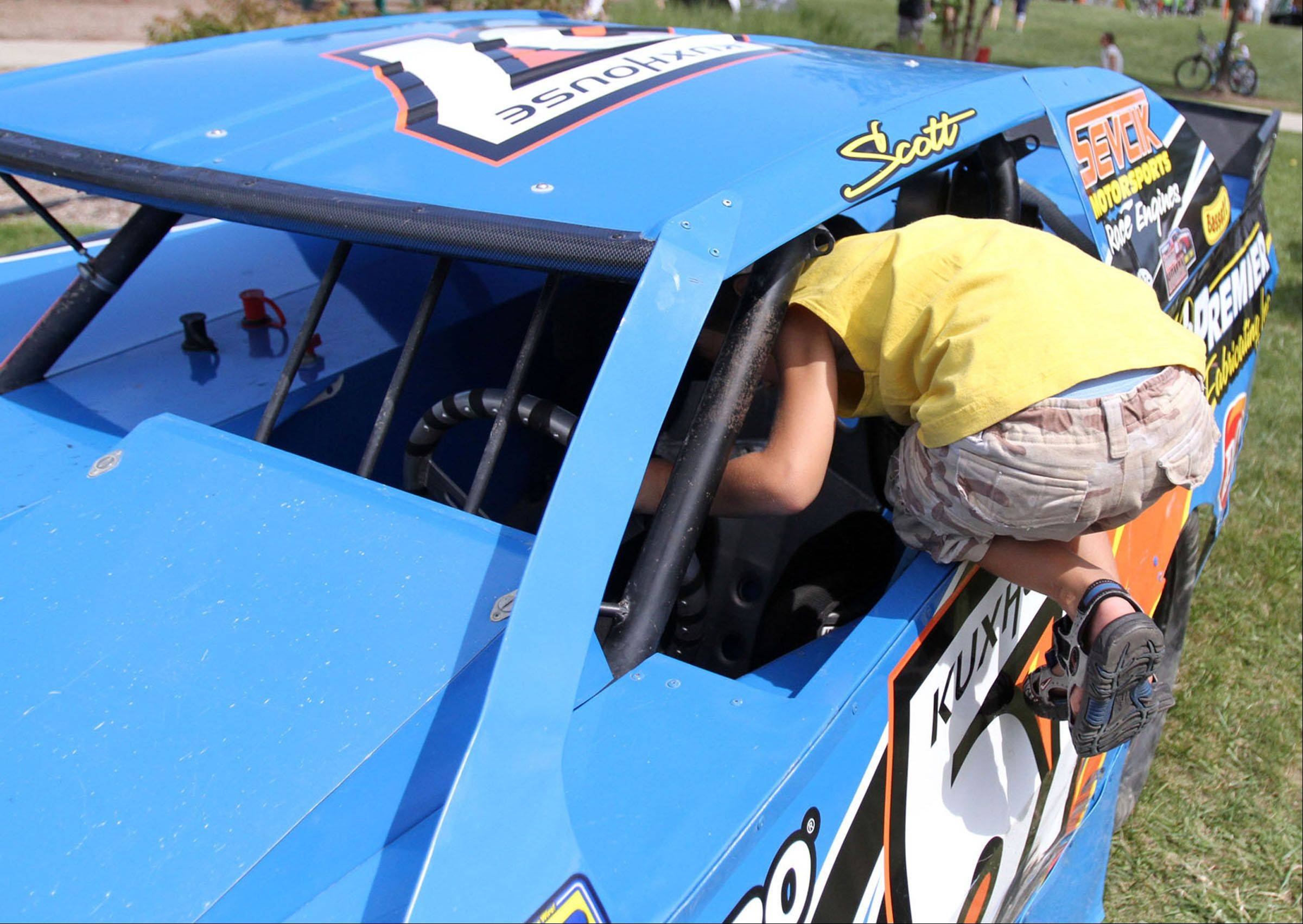 Troy Hensley, 5, of Lake Villa tries to climb into dirt modified stock car owned by Scott Kuxouse of Antioch and on display at Hainesville Fest at Union Square Park on Saturday.