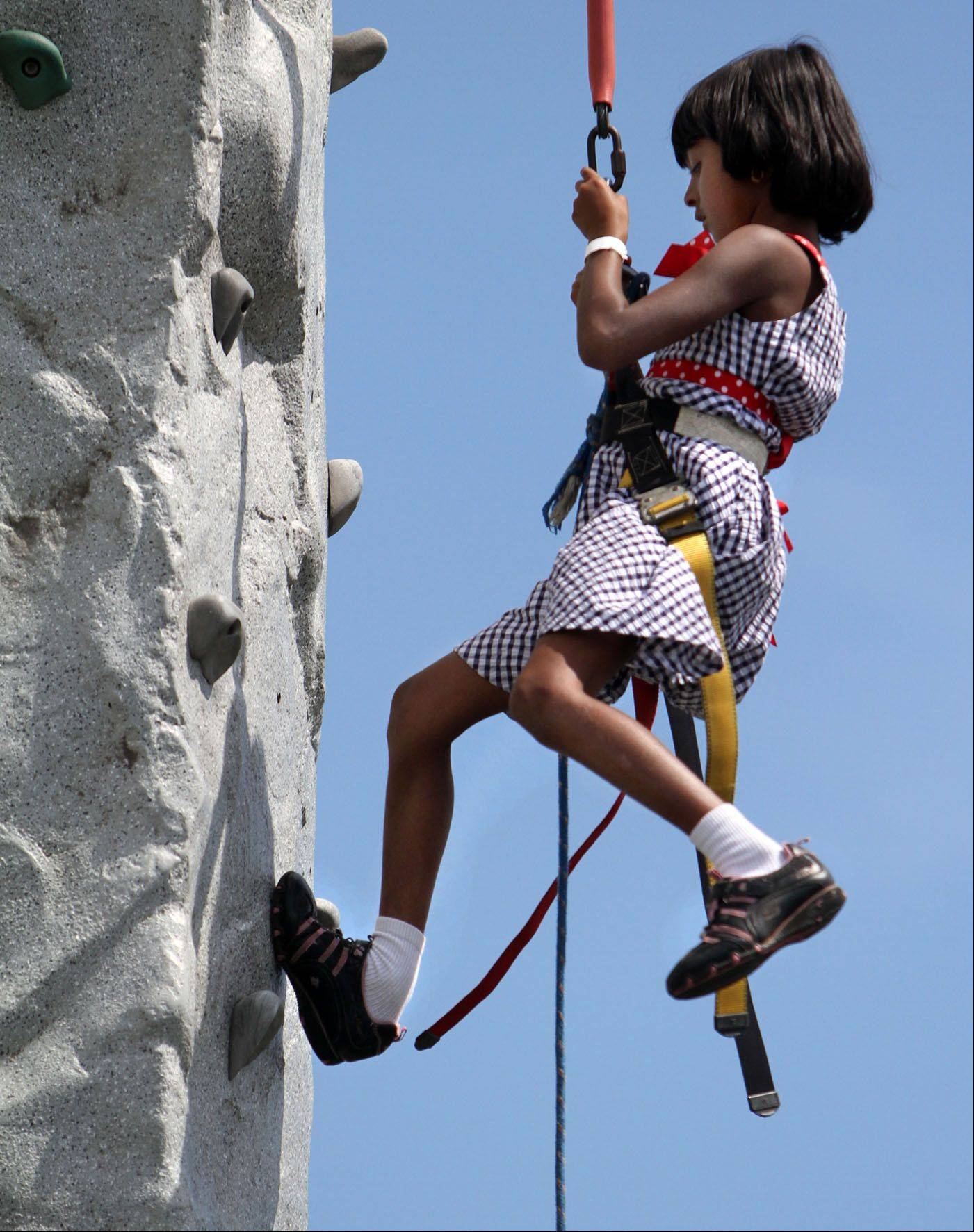 Suhani Peramanu, 7, of Hainesville makes it to the top of the Awesome Amusements climbing wall at Hainesville Fest at Union Square Park on Saturday.