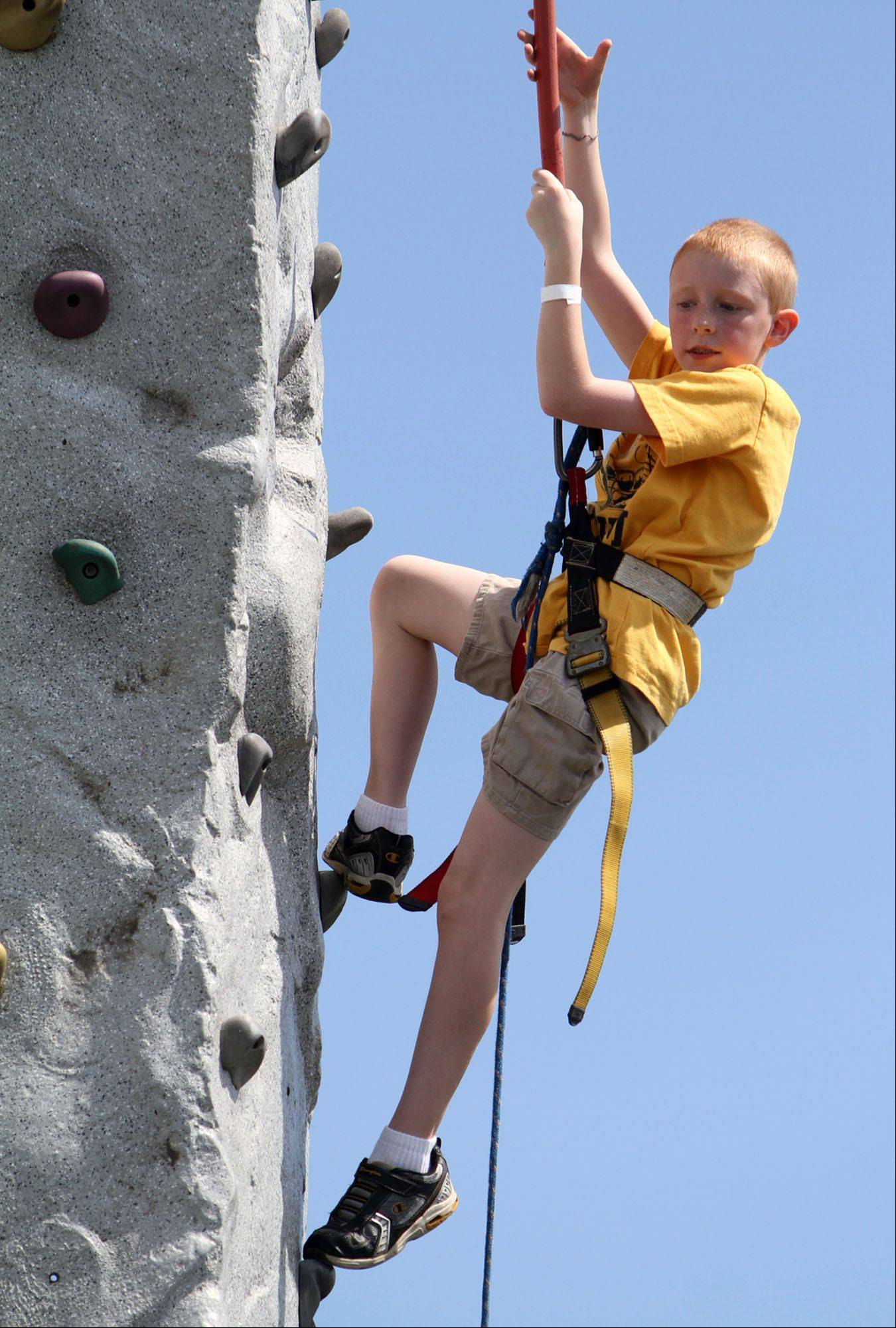 Tommy Jakubowski, 9, of Hainesville climbs the Awesome Amusements climbing wall at Hainesville Fest at Union Square Park on Saturday.