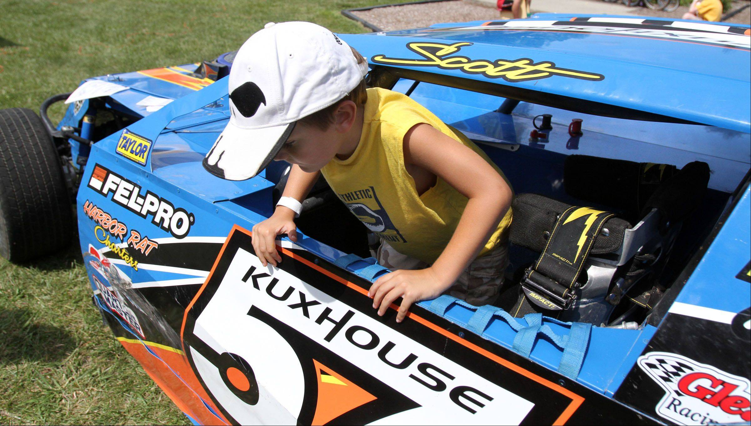 Troy Hensley, 5, of Lake Villa climbs out of a dirt modified stock car owned by Scott Kuxouse of Antioch and on display at Hainesville Fest at Union Square Park on Saturday.