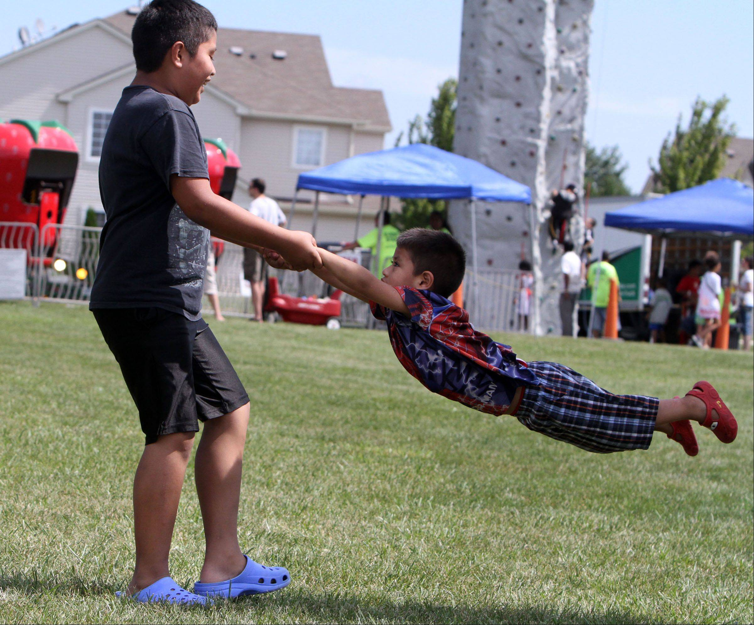 Jesse Vargas, 9, swings his brother Keven, 3, both of Round Lake Beach enjoy a picnic at Hainesville Fest at Union Square Park on Saturday.
