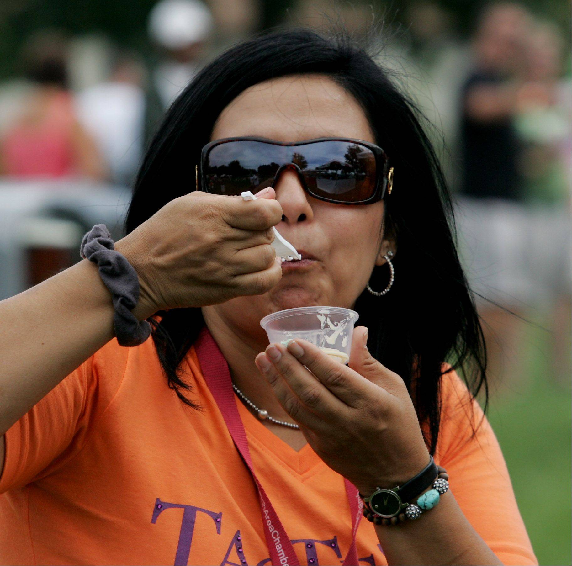 Hanan Hafez of Lake Zurich tastes the Chicken Beurre Blanc from On Occasion Catering during the 5th Annual Taste of the Towns Sunday at Paulus Park in Lake Zurich.