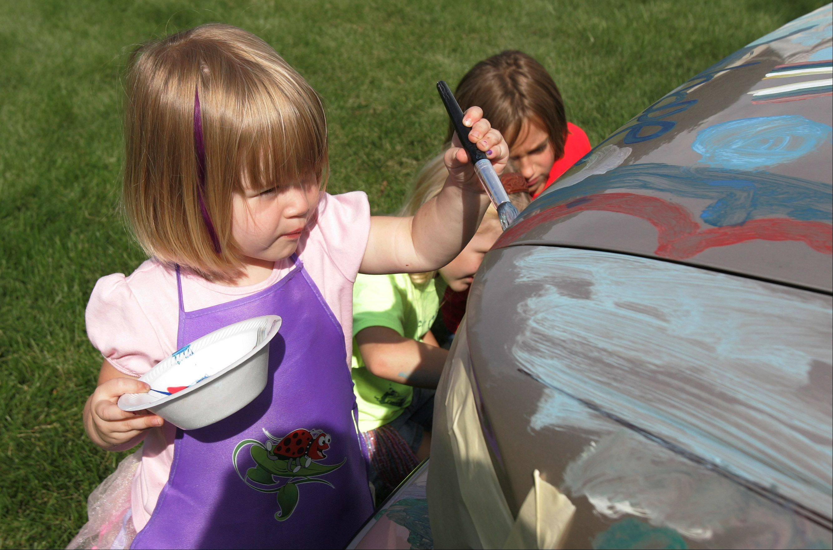 Naiomi Herrman, 3, of Lake Zurich paints on a car during the 5th Annual Taste of the Towns Sunday at Paulus Park in Lake Zurich.