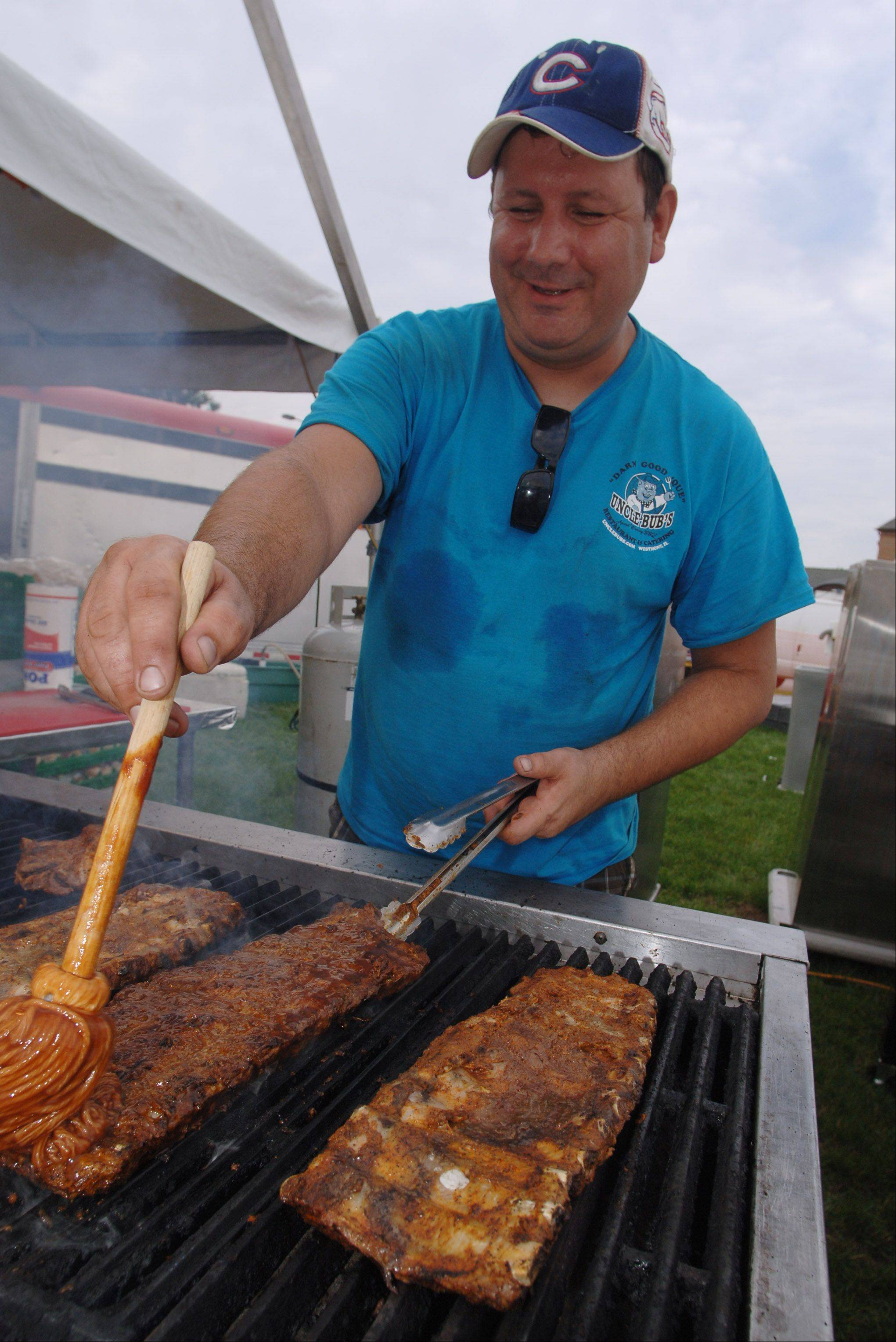 Paul Myers of Uncle Bub's ribs cooks at the inaugural Little Bear Ribfest Friday night in Vernon Hills. Food, drink and music are all part of this fest in Century Park.