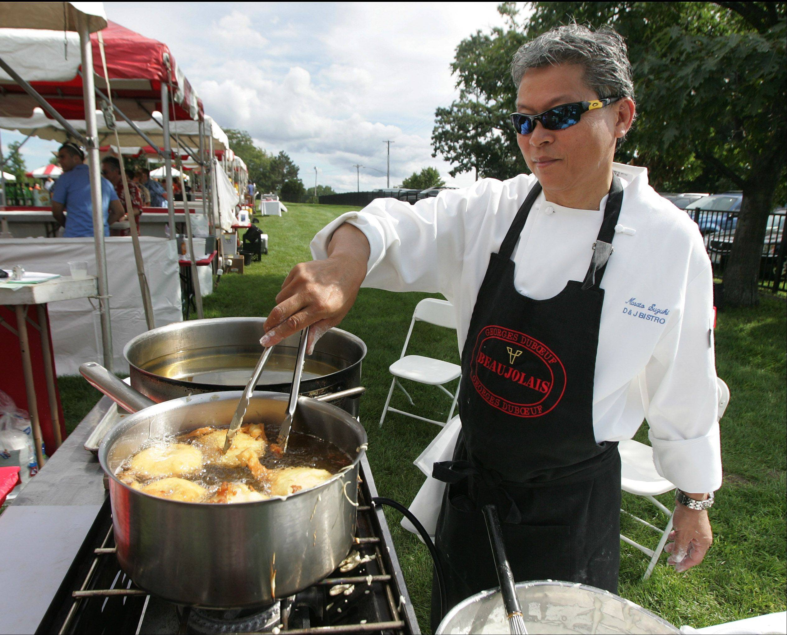 Masato Suzuki of D & J Bistro makes Beignet au Pomme during the 5th Annual Taste of the Towns Sunday at Paulus Park in Lake Zurich.