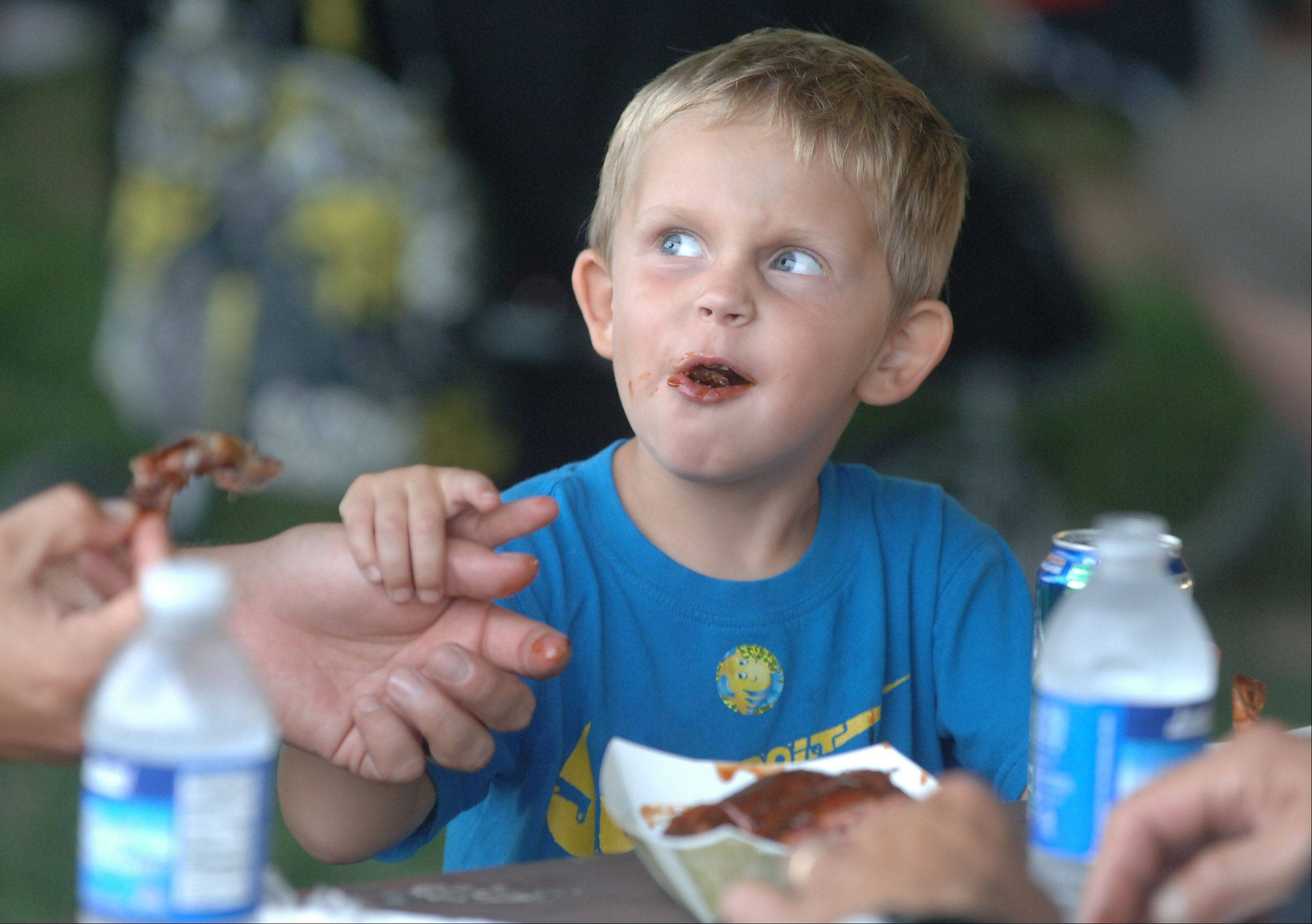 Thorsten Papak, 4 of Vernon Hills, enjoys ribs with his dad, Ryan Papak, during the inaugural Little Bear Ribfest Friday in Vernon Hills at Century Park.