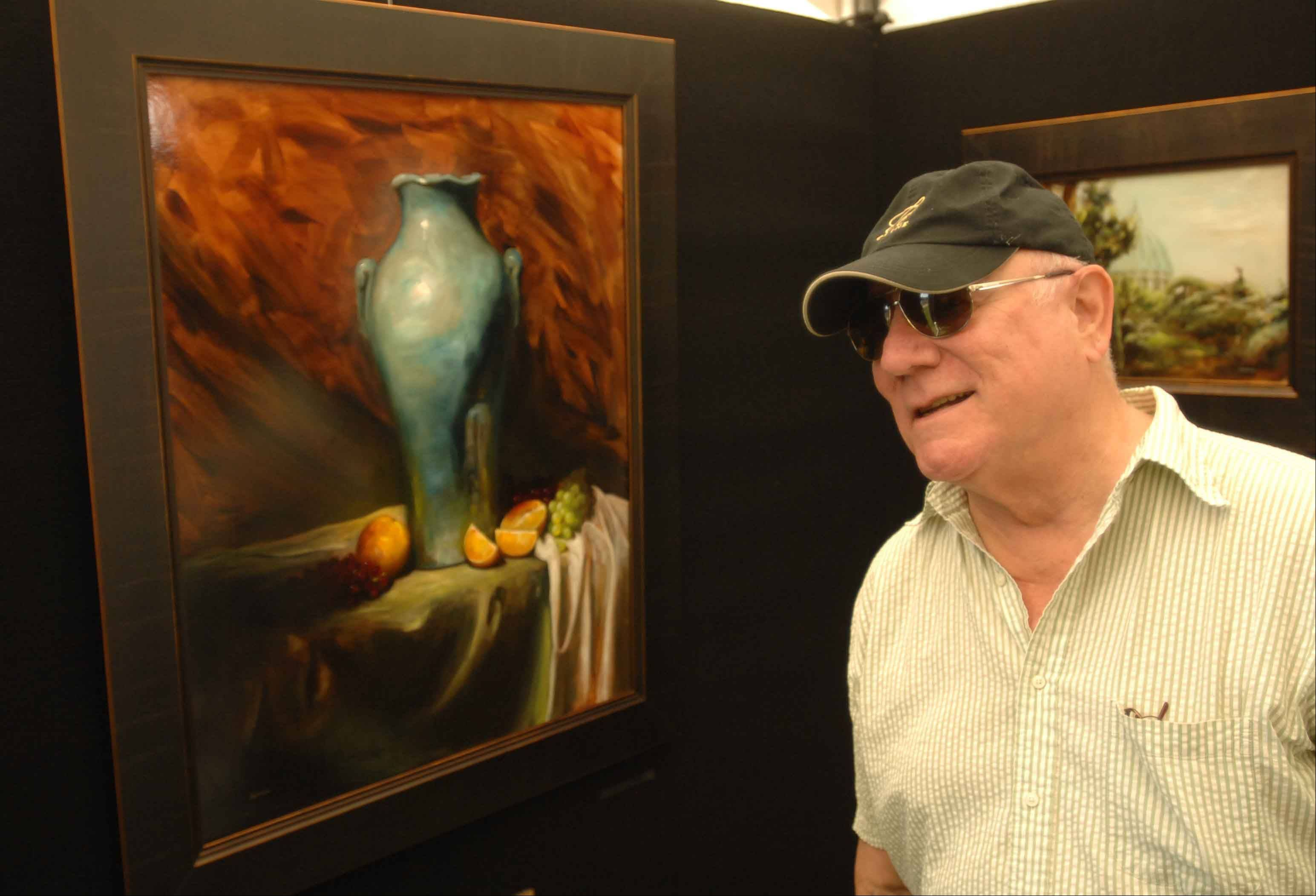 Steve Roe of Lombard looks at art by George Ceffalio during the Glen Ellyn Festival of the Arts at Lake Ellyn Park Saturday.