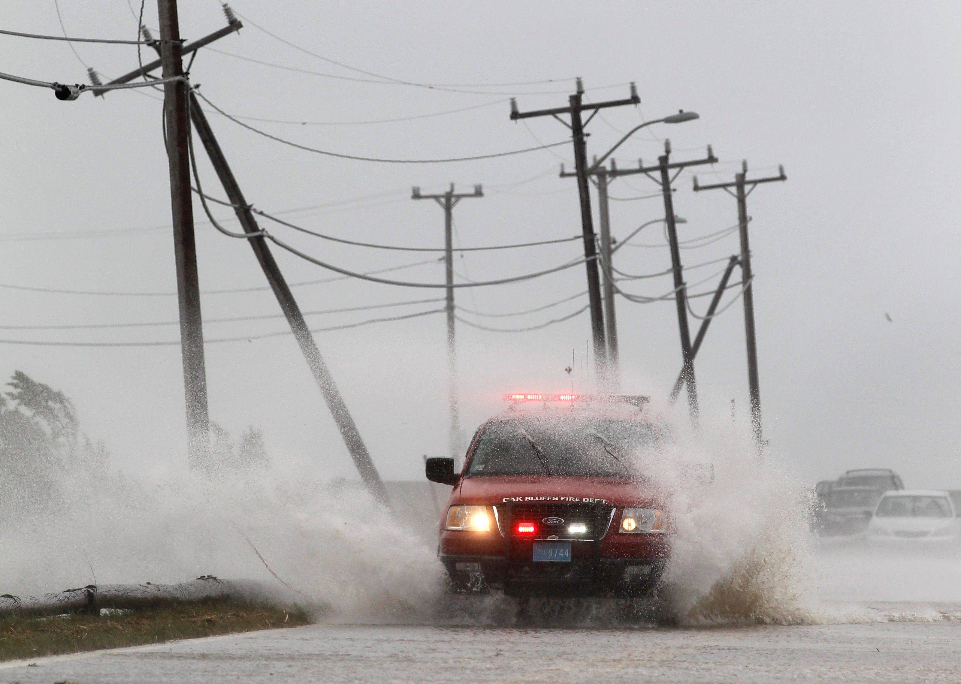 An Oak Bluffs fire department vehicle is buffeted by strong winds and ocean spray from Tropical Storm Irene while driving along a costal road in Edgartown, Mass., on the island of Martha's Vineyard, Sunday, Aug. 28, 2011.