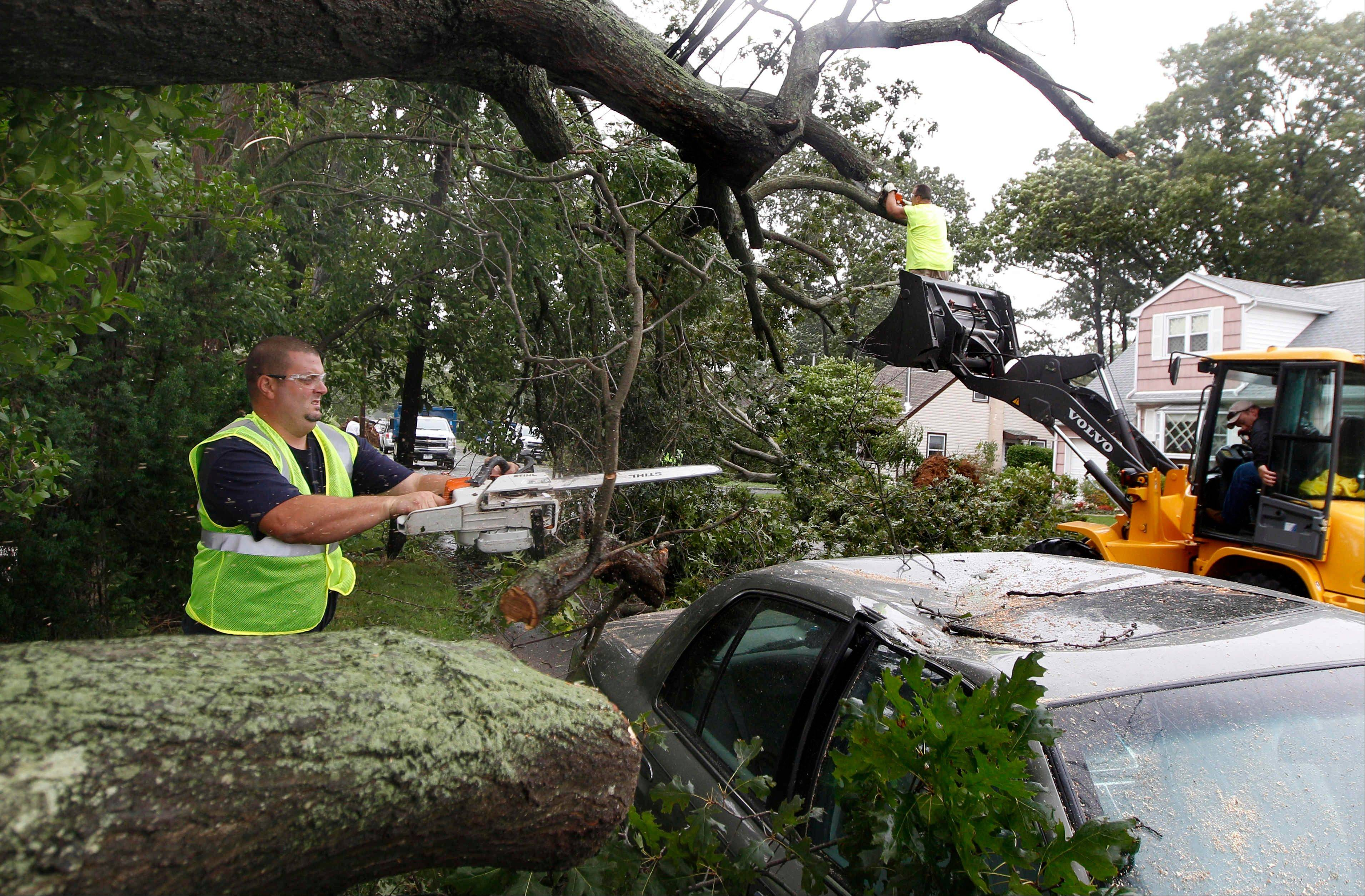 Workers clear trees that fell on power lines and cars after the effects of Hurricane Irene in Amittyville, N.Y., on Long Island, Sunday, Aug. 28, 2011.