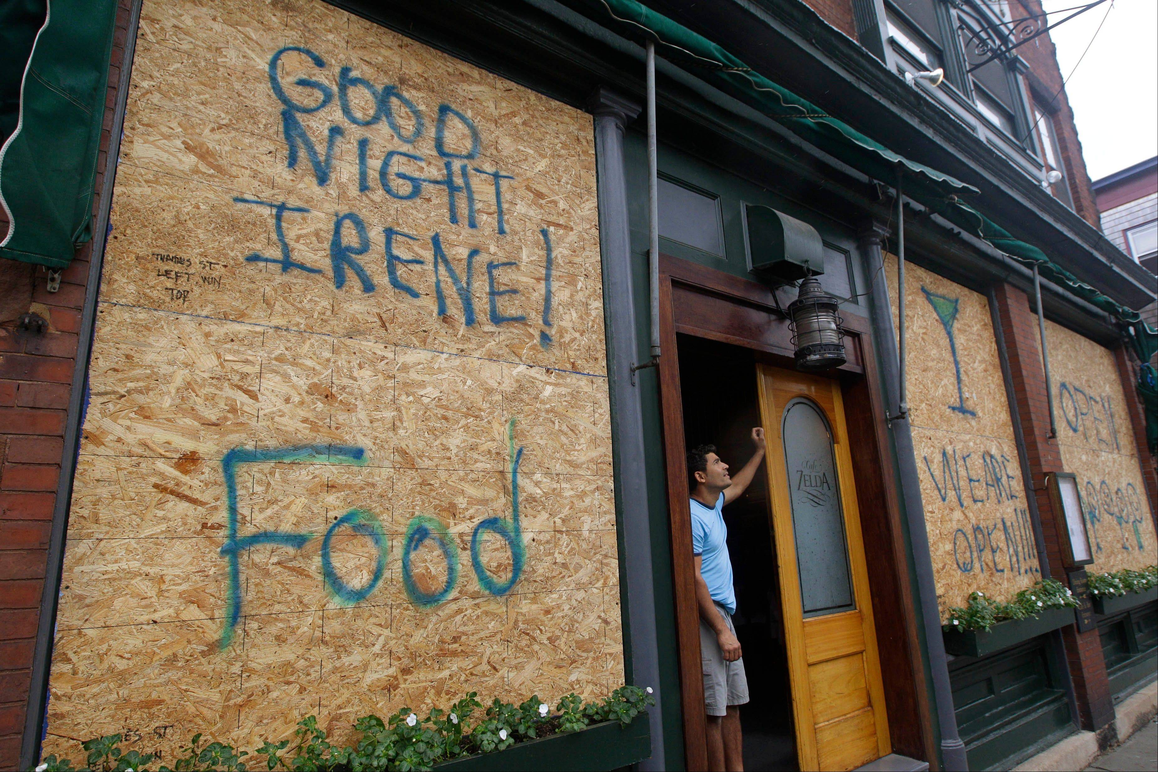 Hernani Abreu stands in the dorrway of Cafe Zelda on historic Tames Street, where he has worked for the past 12 years, and looks up at the sky as Tropical Storm Irene impacts the area in Newport, RI., Sunday morning, Aug. 28, 2011. Irene weakened to winds of 60 mph, well below the 74 mph dividing line between a hurricane and tropical storm. The system was still massive and powerful, forming a figure six that covered the Northeast. It was moving twice as fast as the day before.