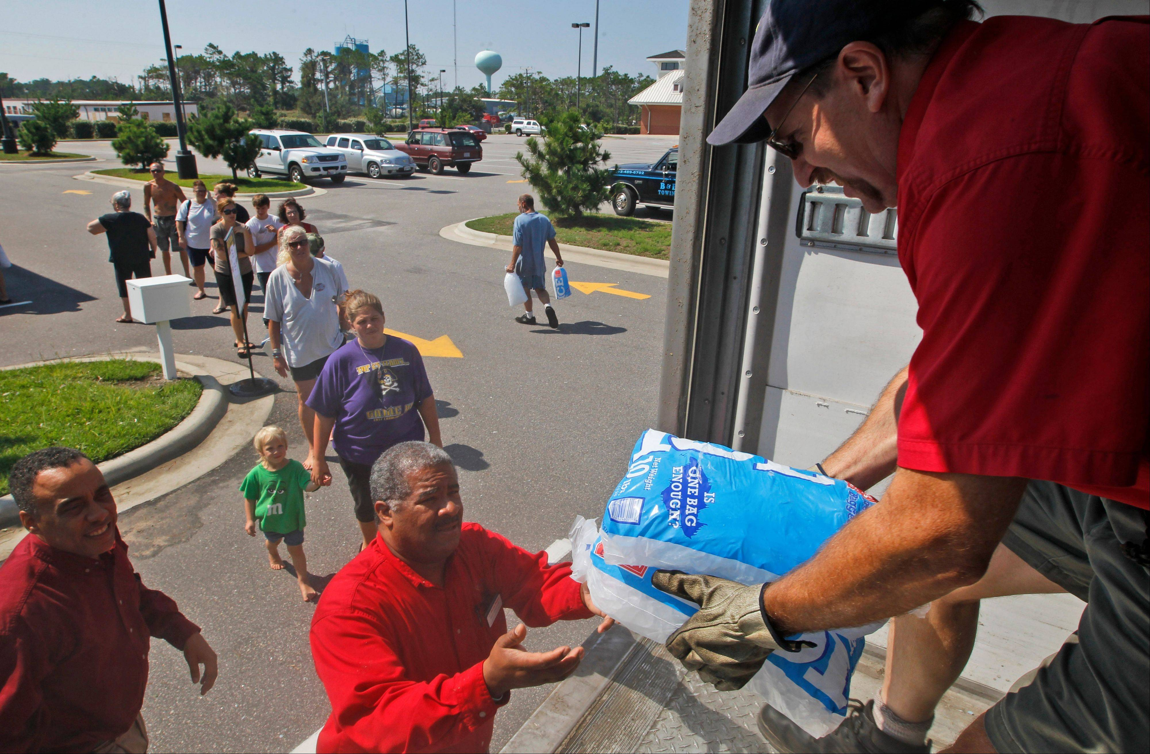 Steve Davenport, right, Ray Brown, center, and Marvin Franklin, left, of Harris Teeter supermarket, hand out free bags of ice from a truck as residents queue up as many people are still without power on the Outer Banks in Kill Devil Hills, N.C., Sunday, Aug. 28, 2011 in the aftermath of Hurricane Irene after it left the North Carolina coast.