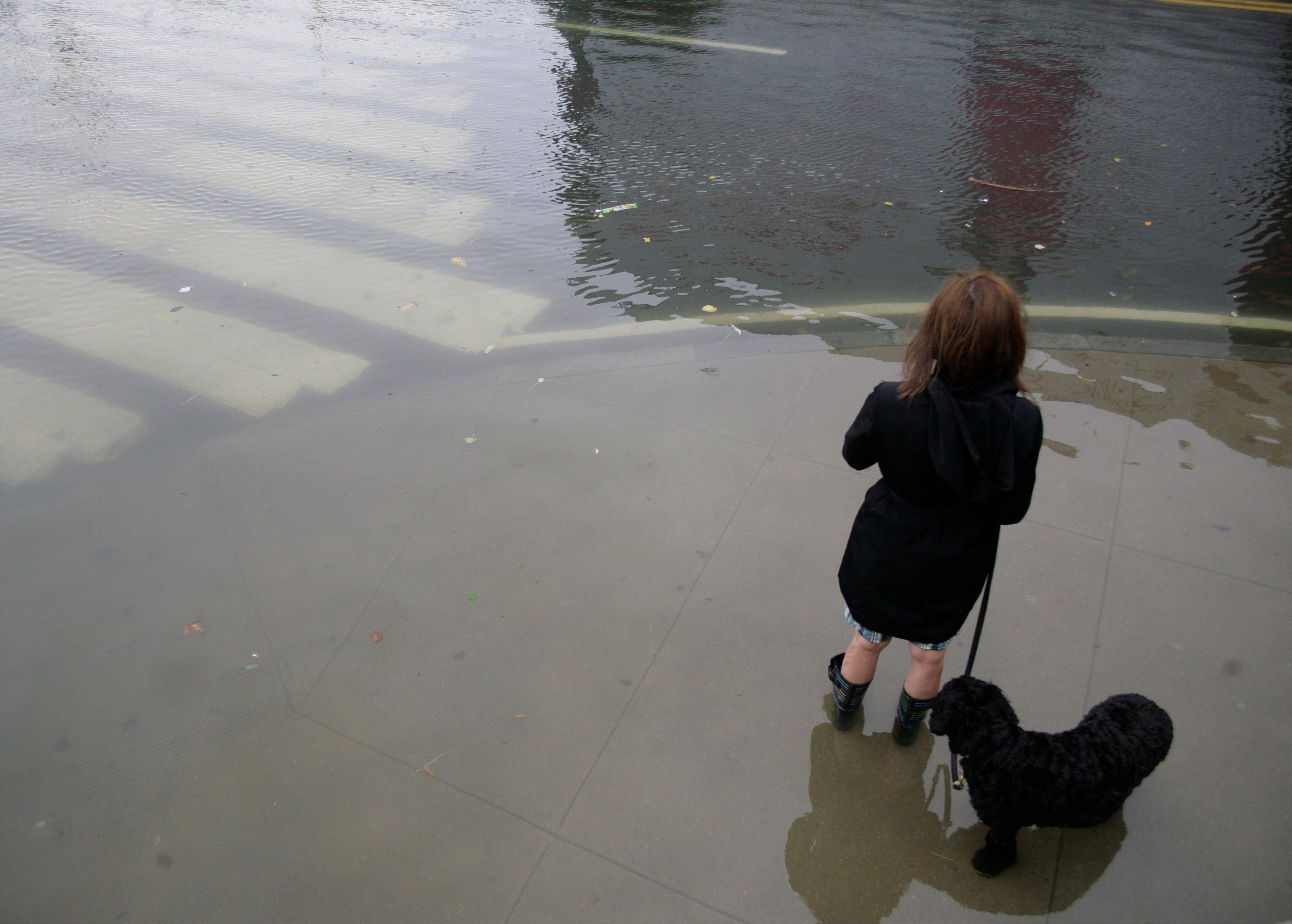 A woman walking a dog contemplates the deep water on Manhattan�s West Side as Tropical Storm Irene passes through the city, Sunday, Aug. 26, 2011 in New York. Although downgraded from a hurricane to a tropical storm, Irene�s torrential rain couple with high winds and tides worked in concert to flood parts of the city.
