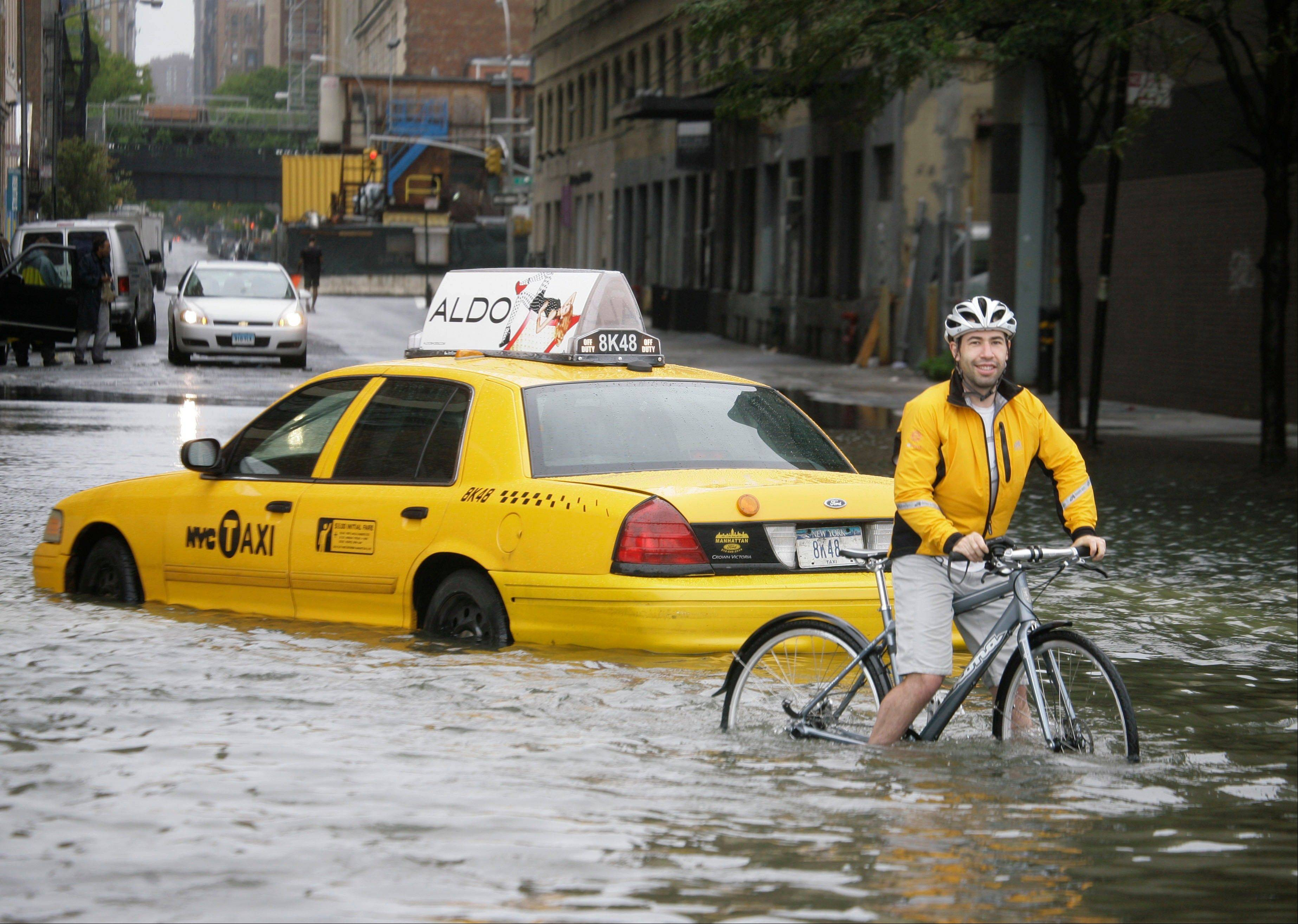 A bicyclist makes his way past a stranded taxi on a flooded New York City Street as Tropical Storm Irene passes through the city, Sunday, Aug. 28, 2011. Although downgraded from a hurricane to a tropical storm, Irene's torrential rain coupled with high winds and tides worked in concert to flood parts of the city.