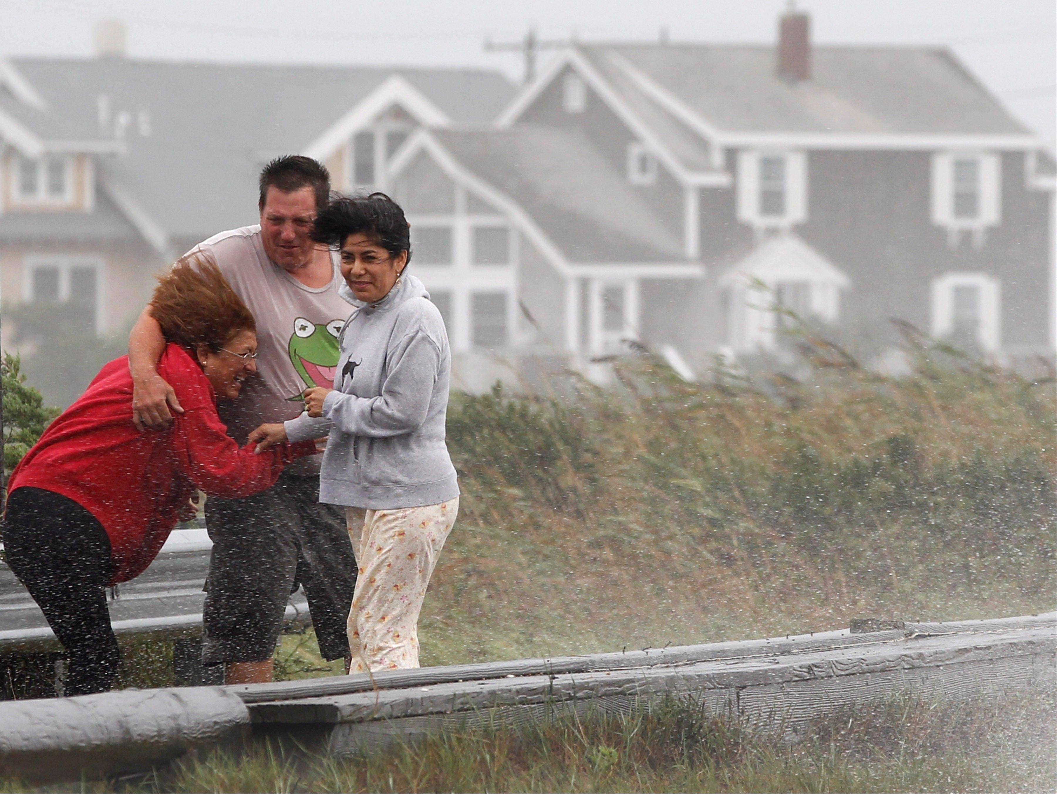 Peter Monaco, of Dunstable, Mass., center, and two unidentified women are buffeted by strong winds from Tropical Storm Irene as they walk along a costal road in Edgartown, Mass., on the island of Martha's Vineyard, Sunday, Aug. 28, 2011. Tropical Storm Irene's gusty winds and rain caused thousands of power outages and flooding Sunday as Massachusetts emergency officials warned that the downgraded storm still posed a significant threat.