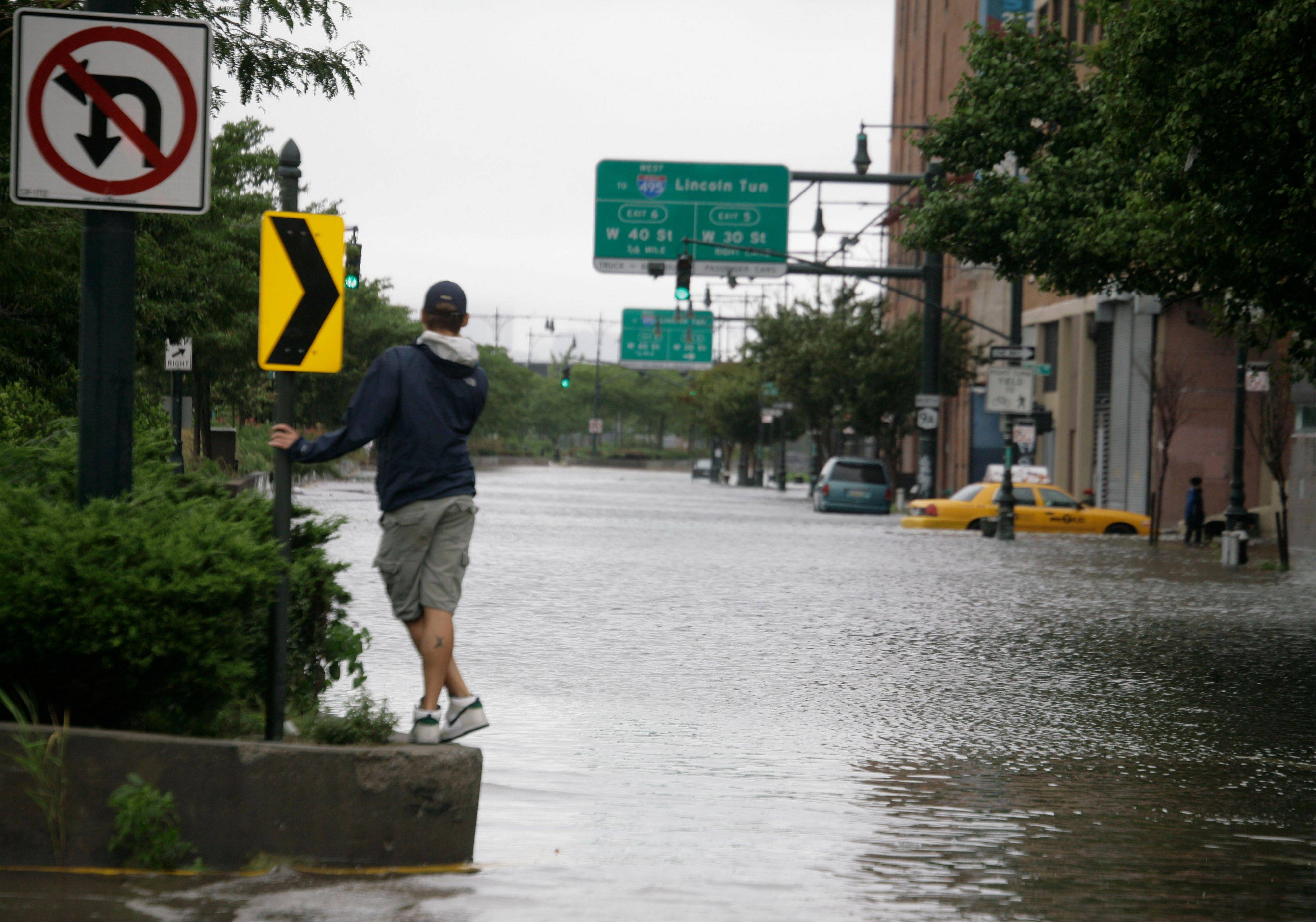 A man surveys the deep water on Manhattan�s West Side as Tropical Storm Irene passes through the city, Sunday, Aug. 28, 2011 in New York. Although downgraded from a hurricane to a tropical storm, Irene�s torrential rain couple with high winds and tides worked in concert to flood parts of the city.