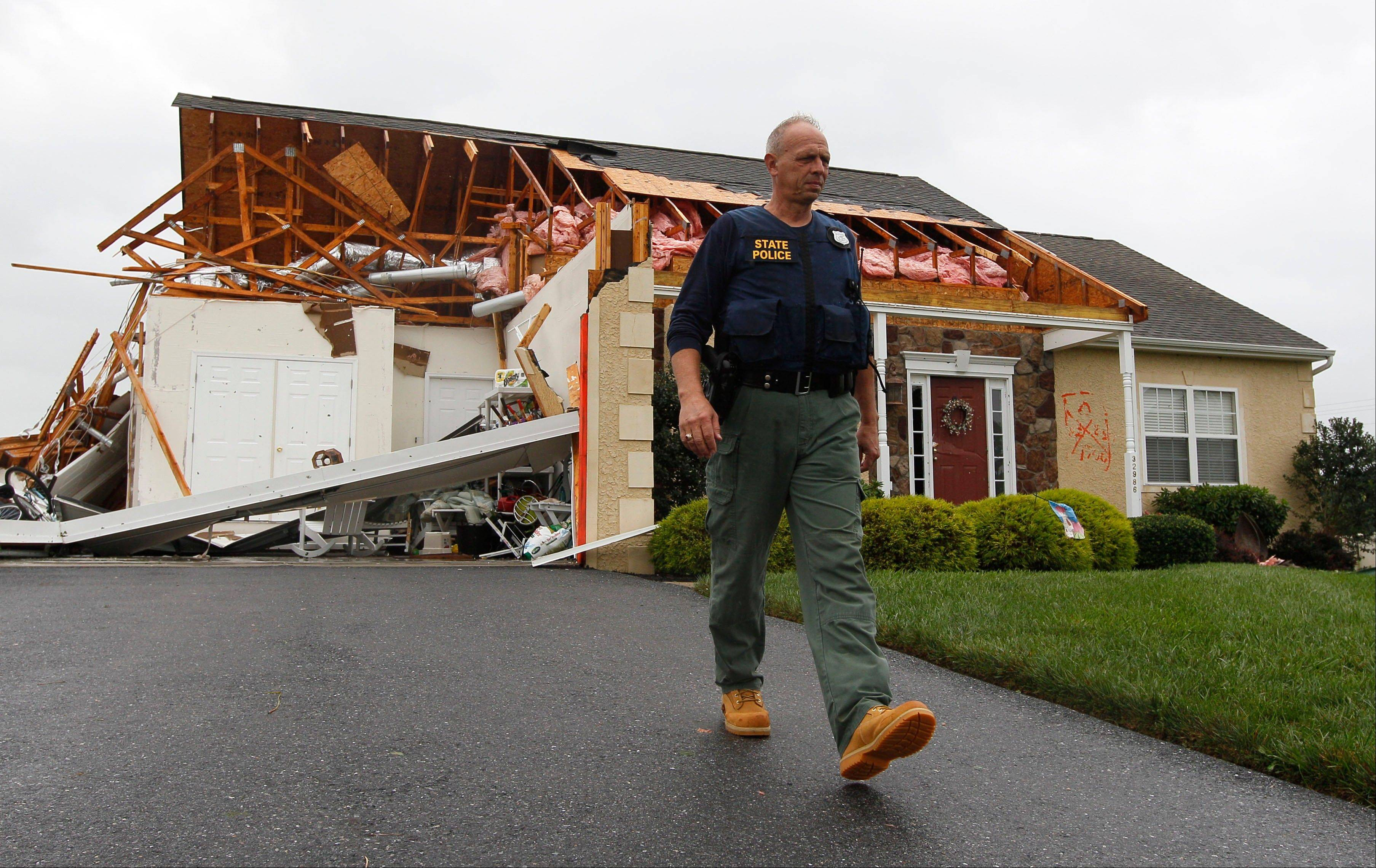 A member of the Delaware State Police walks away from a house that was heavily damaged by a possible tornado in Lewes, Del., Sunday, Aug. 28, 2011, after Hurricane Irene churned along the Delaware coast overnight. From North Carolina to New Jersey, Hurricane Irene appeared to have fallen short of the doomsday predictions, but more than 4.5 million homes and businesses along the East Coast reportedly lost power, and at least 11 deaths were blamed on the storm.