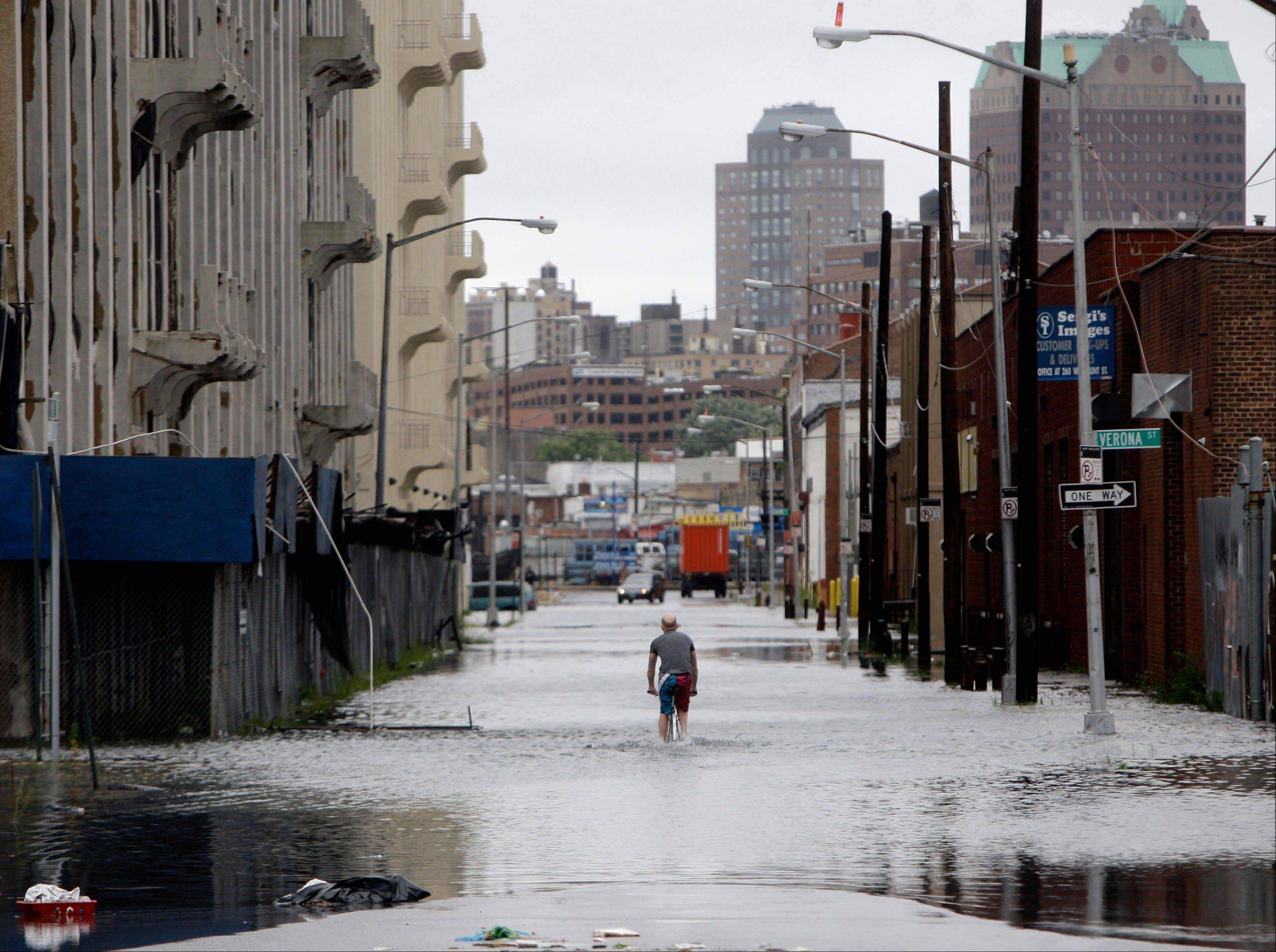 A police officer is parked at the end of a flooded street in Brooklyn, New York, Sunday, Aug. 28, 2011. Seawater surged into the streets of Manhattan on Sunday as Tropical Storm Irene slammed into New York, downgraded from a hurricane but still unleashing furious wind and rain. The flooding threatened Wall Street and the heart of the global financial network.