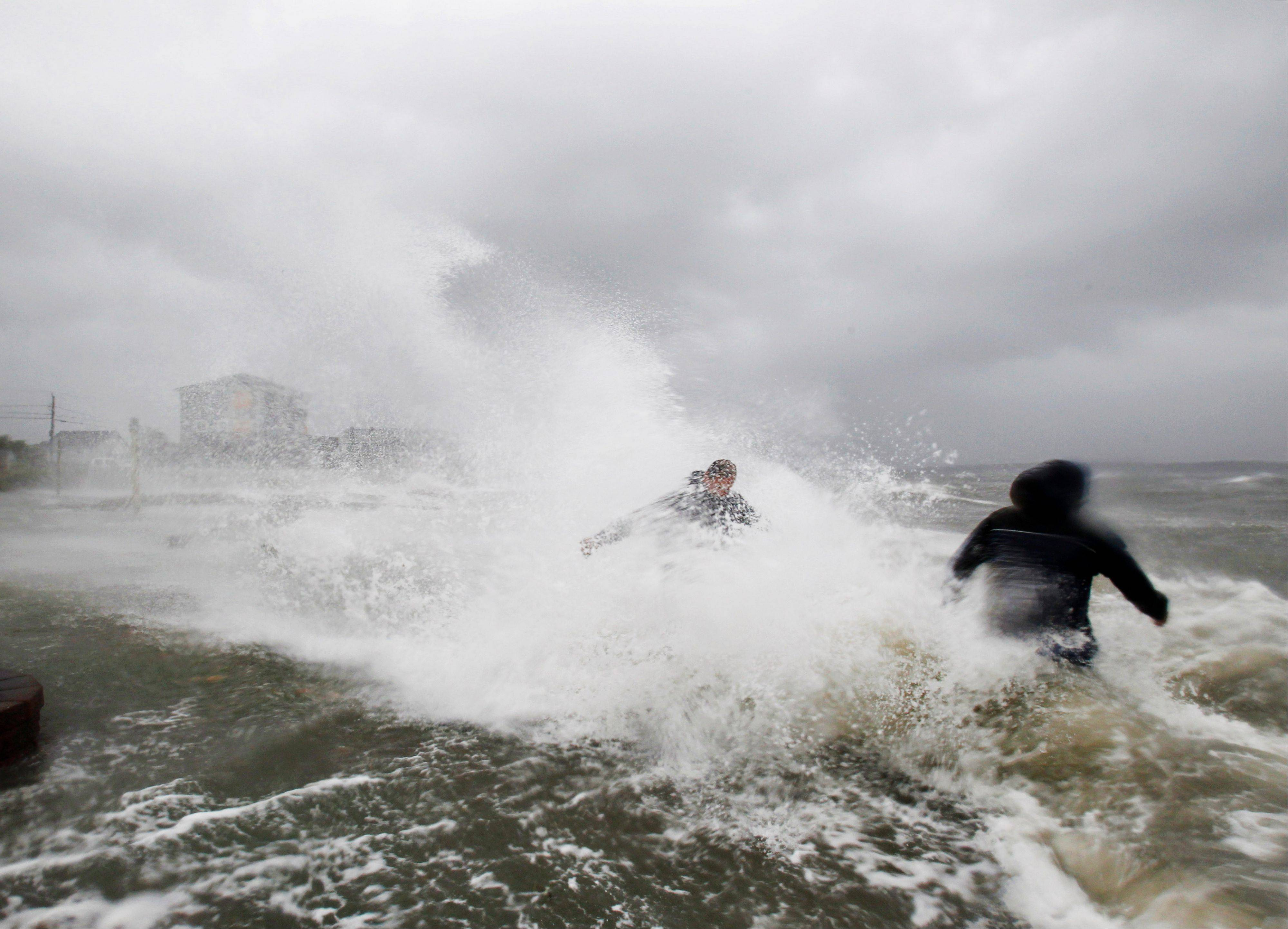 Ken Thompson, right, and Ray Morrison make their way toward their house along a seawall as winds from Tropical Storm Irene batter the shore in Fairhaven, Mass., Sunday, Aug. 28, 2011. Irene weakened to winds of 65 mph, below the 74 mph dividing line between a hurricane and tropical storm. The system was still massive and powerful, forming a figure six that covered the Northeast. It was moving twice as fast as the day before.