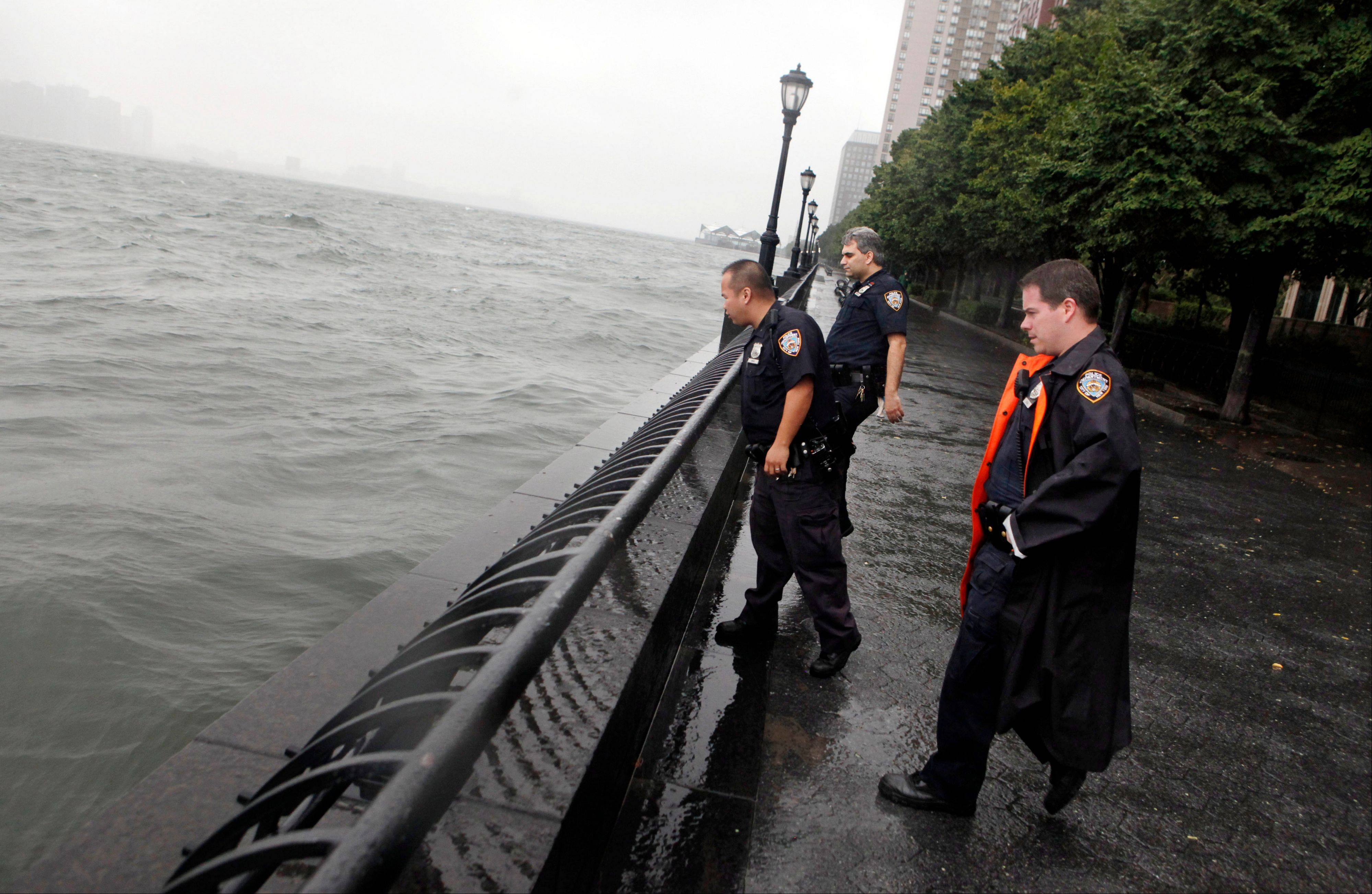 Police officers inspect the water level along the Battery Park City seawall as Tropical Storm Irene passes through New York, Sunday, Aug. 28, 2011. Battery Park City and other areas in Lower Manhattan have been evacuated in advance of the storm.